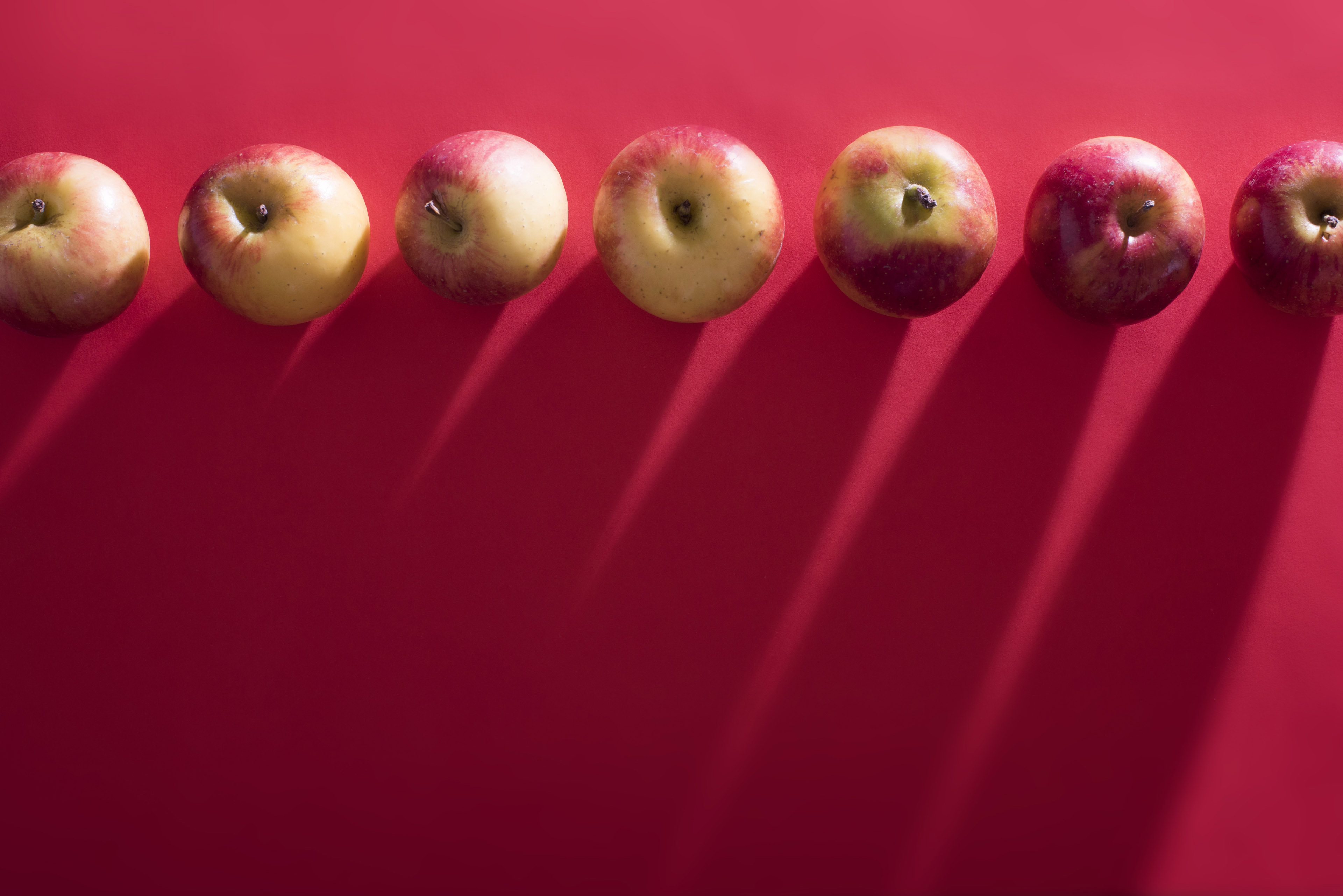 Fresh apples arranged in row on red background with copyspace