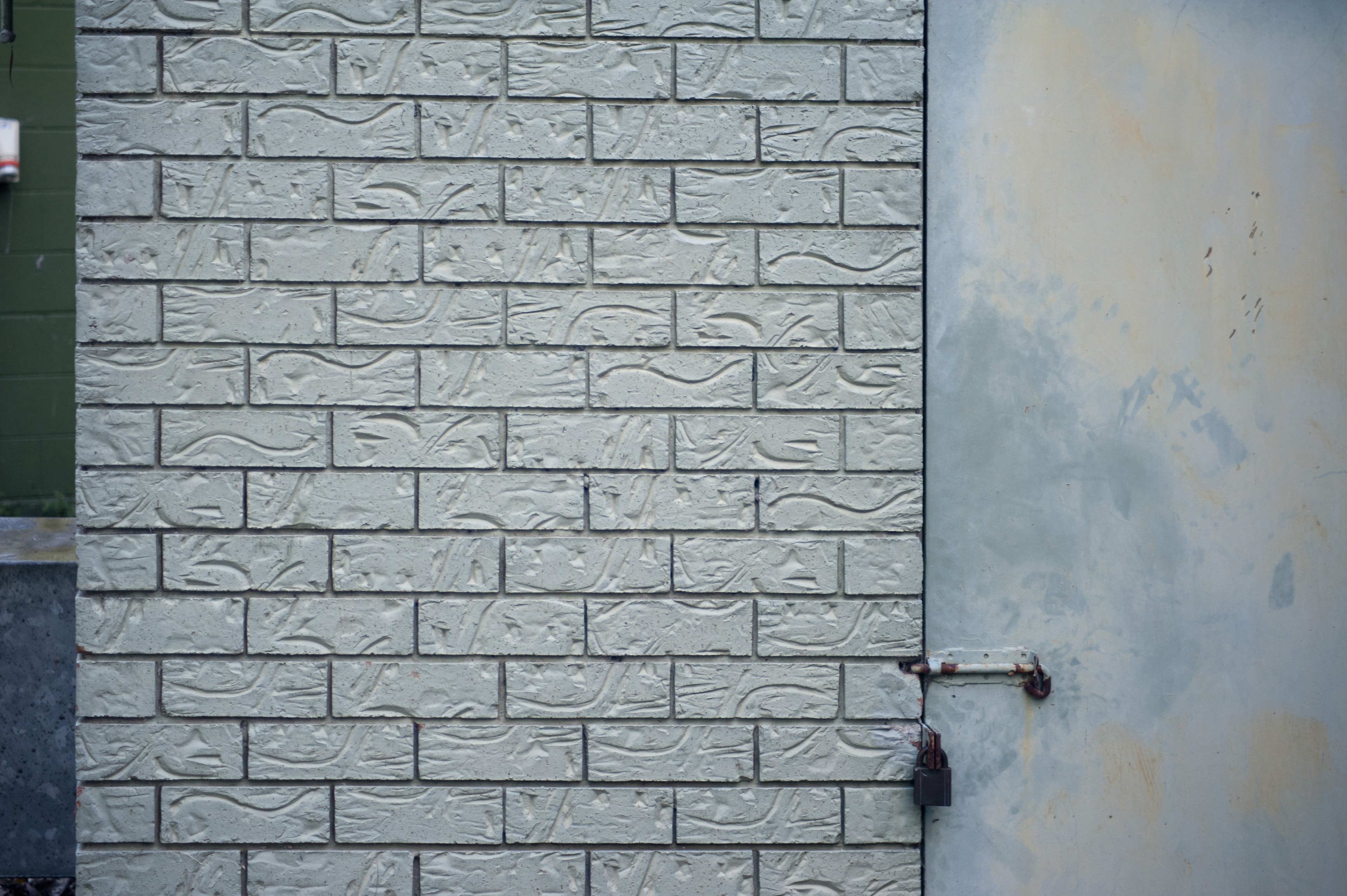 Architectural Detail of White Patterned Brick Wall and Closed Door Secured with Various Locks