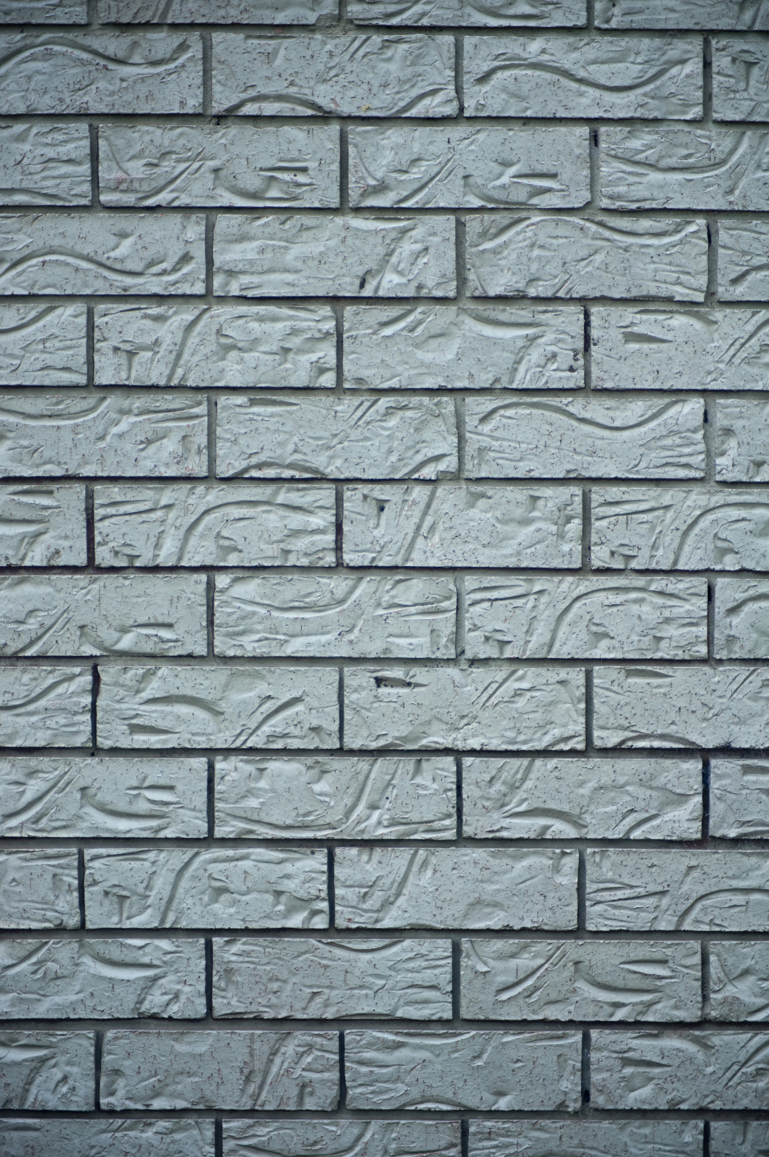 Textured Gray Brick Wall with Abstract Carvings for Background Designs, Emphasizing Copy Space.