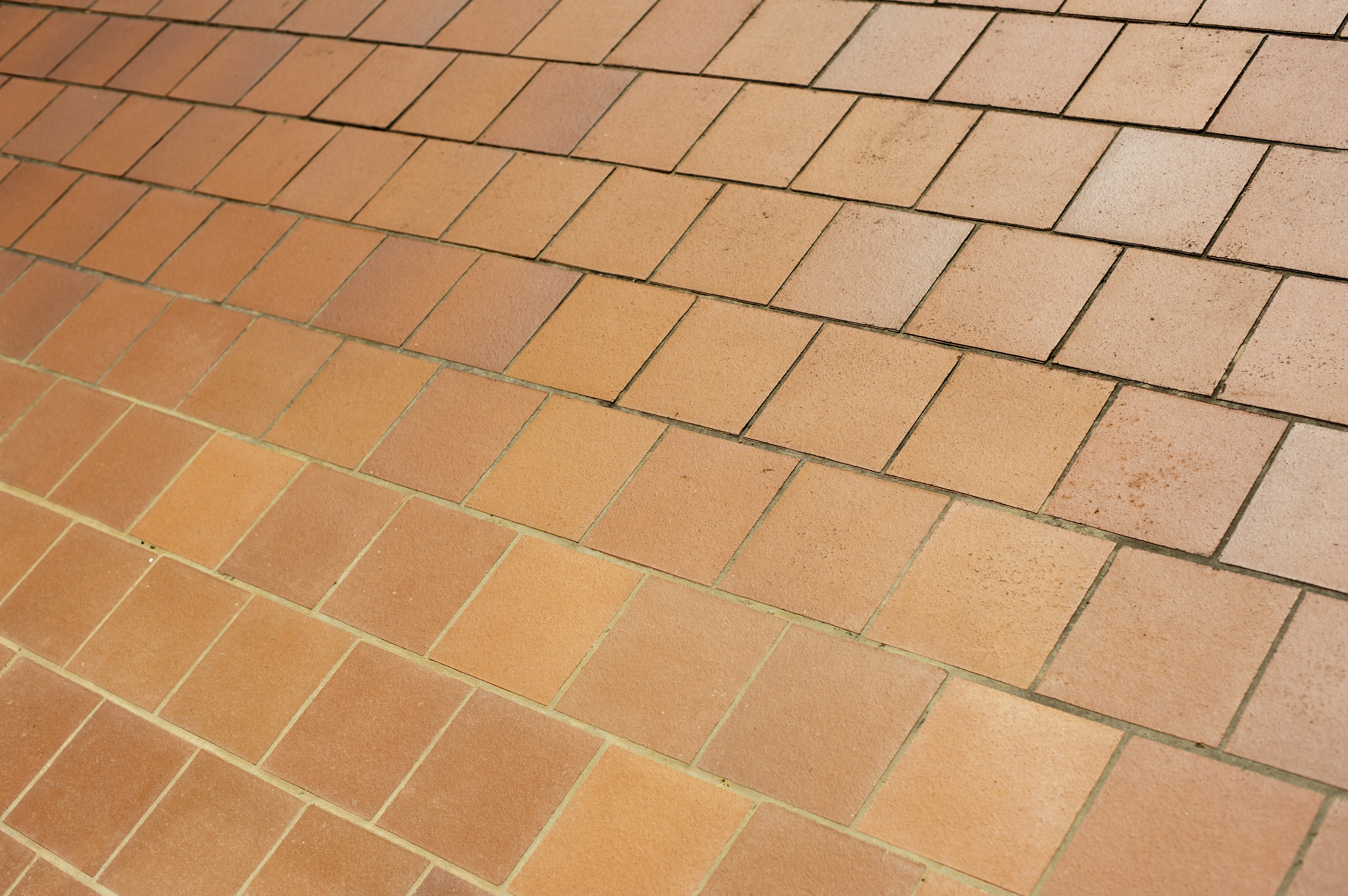 Oblique view of brown ceramic floor tiles in a receding perspective in a full frame architectural background