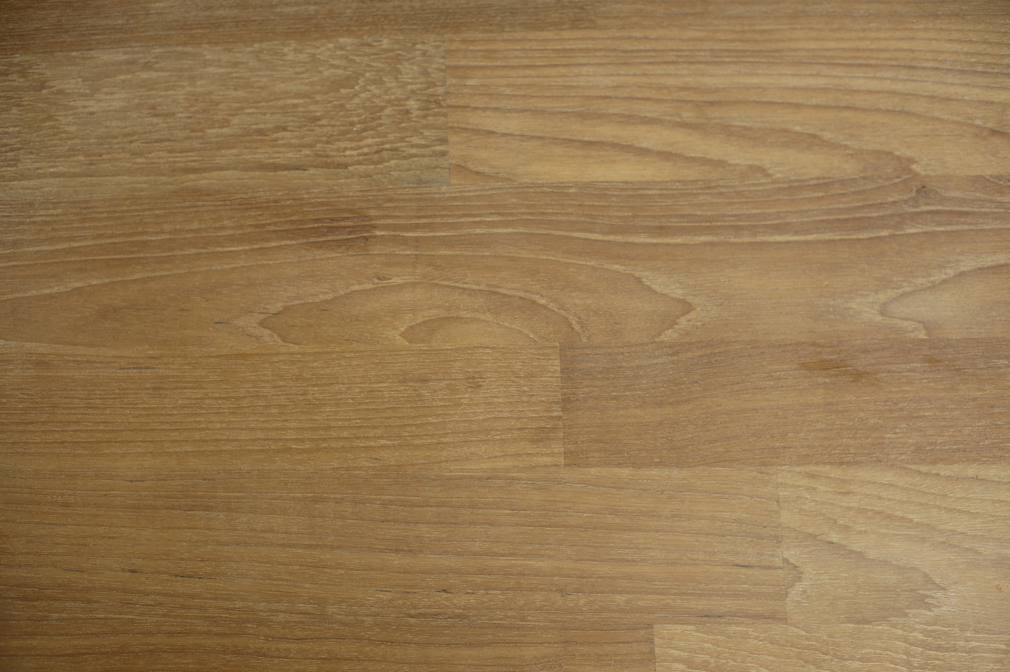 Brown parquet flooring made of horizontal rows of laminate wooden battens, close up