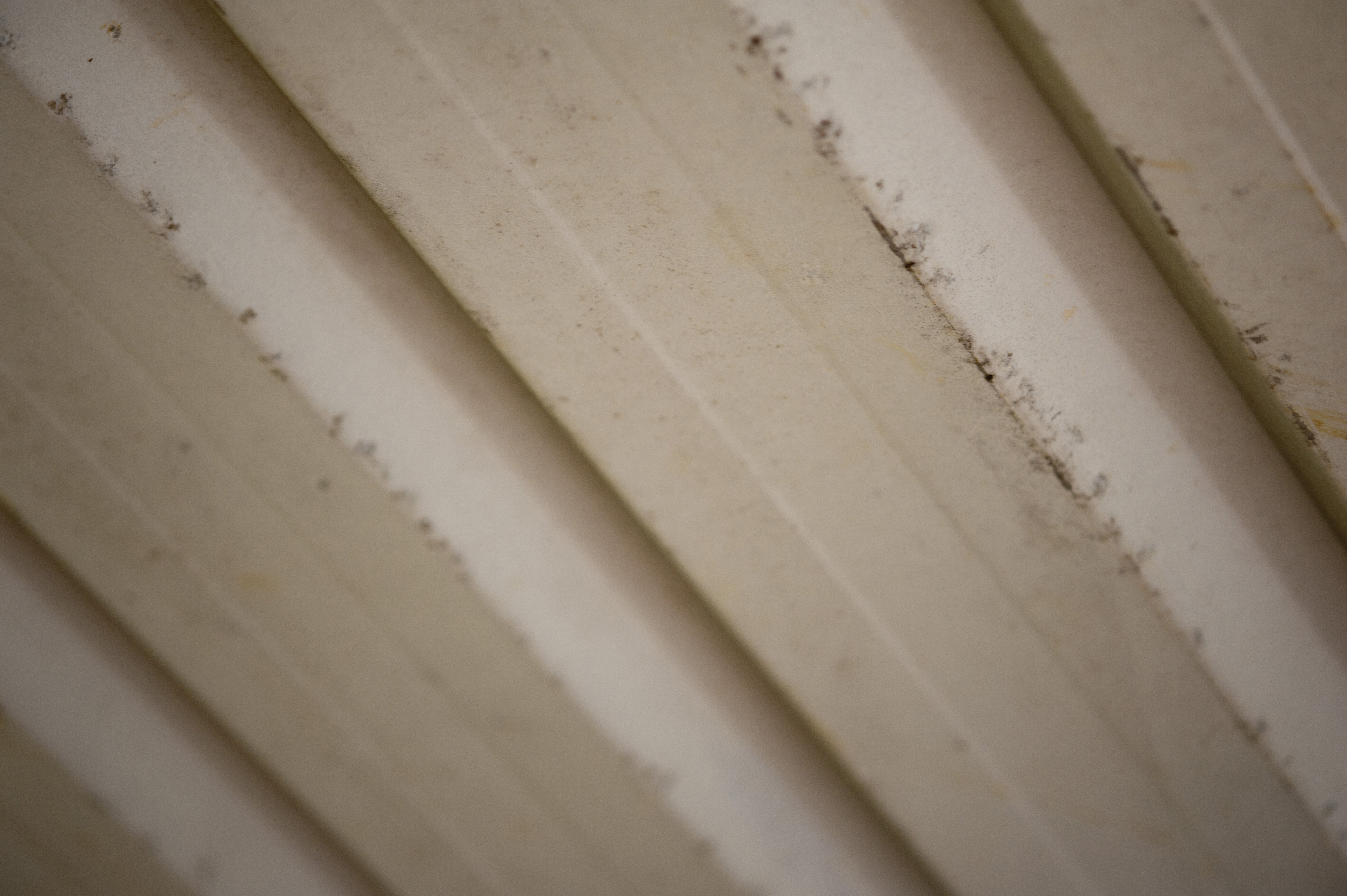 Corrugated metal sheet background with rough worn edges and chipped grunge white paint in an architectural background of building material