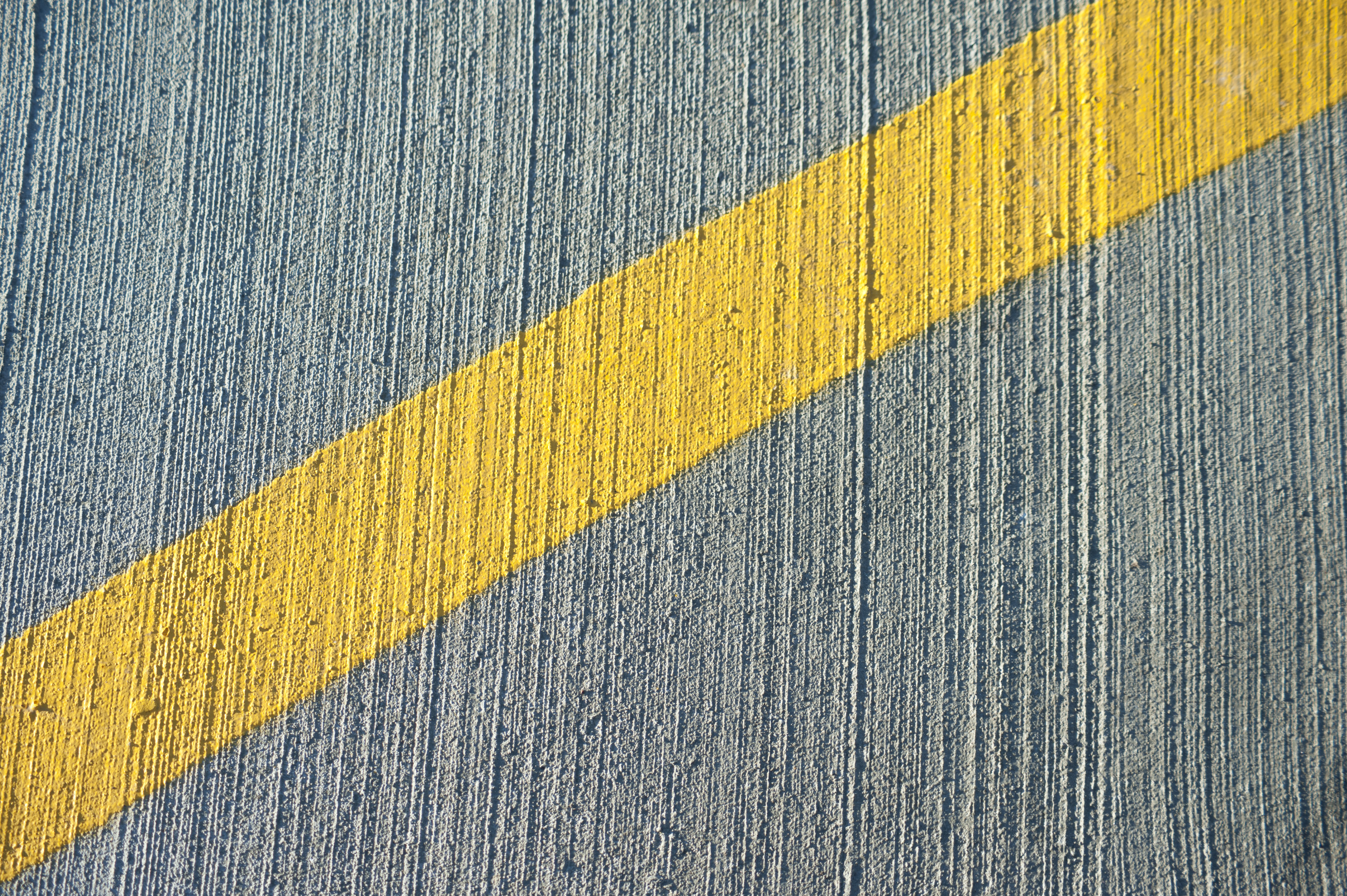 Oblique stripe of yellow paint marked on irregular gray concrete wall, close-up