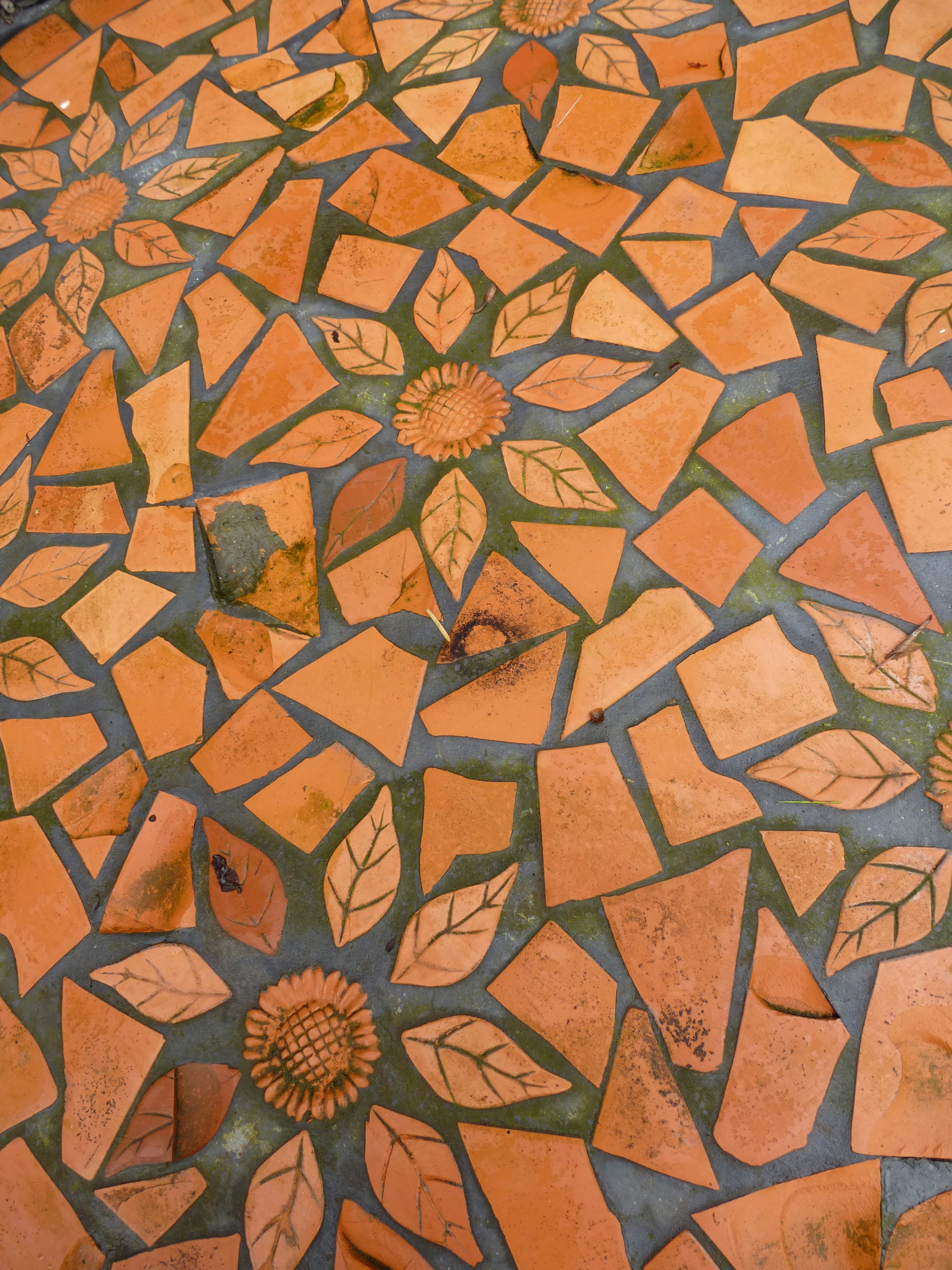 Crazy paving background texture and pattern with decorative floral inlay in a rich brown color, overhead view of the floor