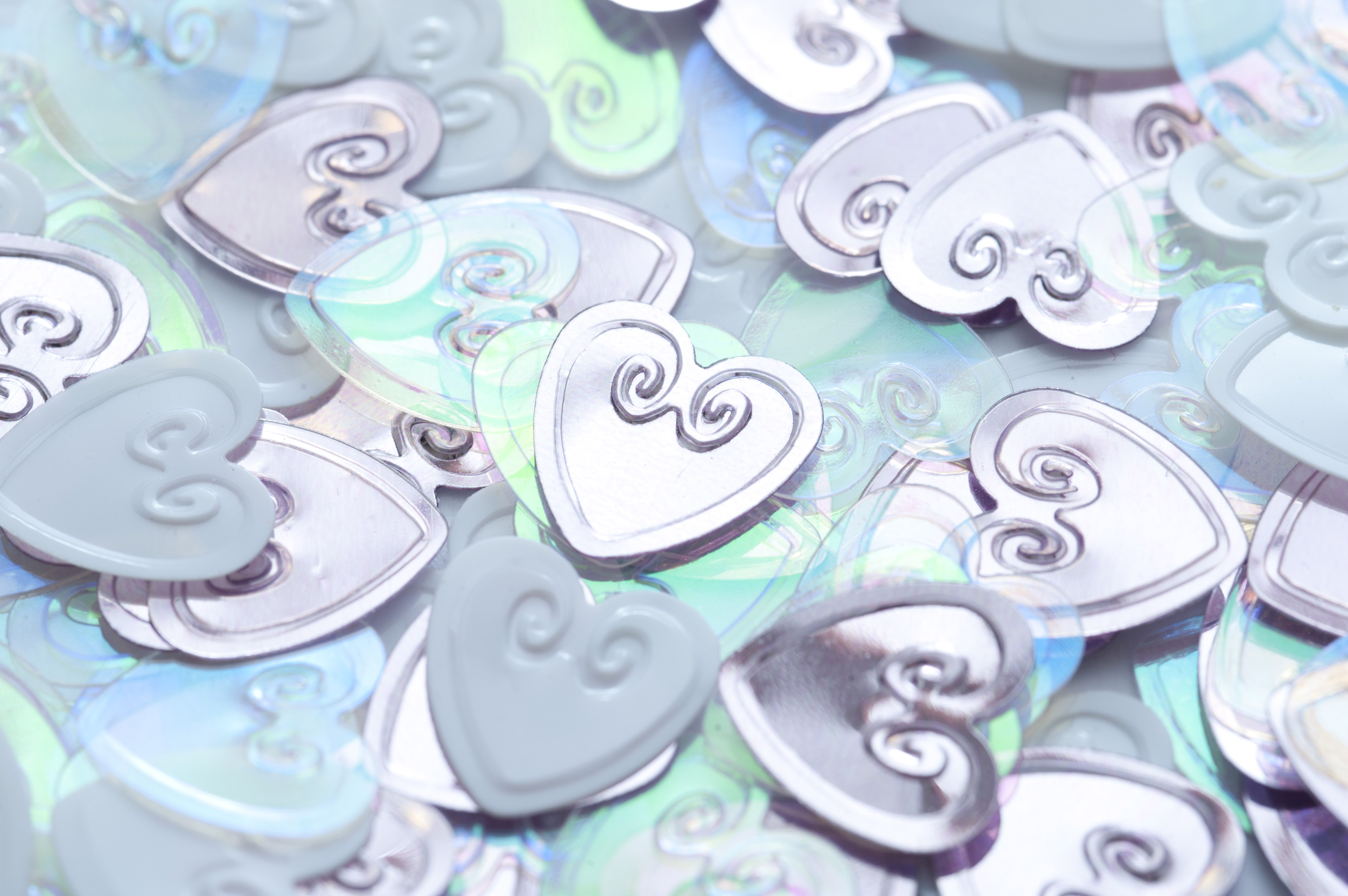 Scattered collection of silver wedding hearts in a close up full frame view symbolic of love and romance
