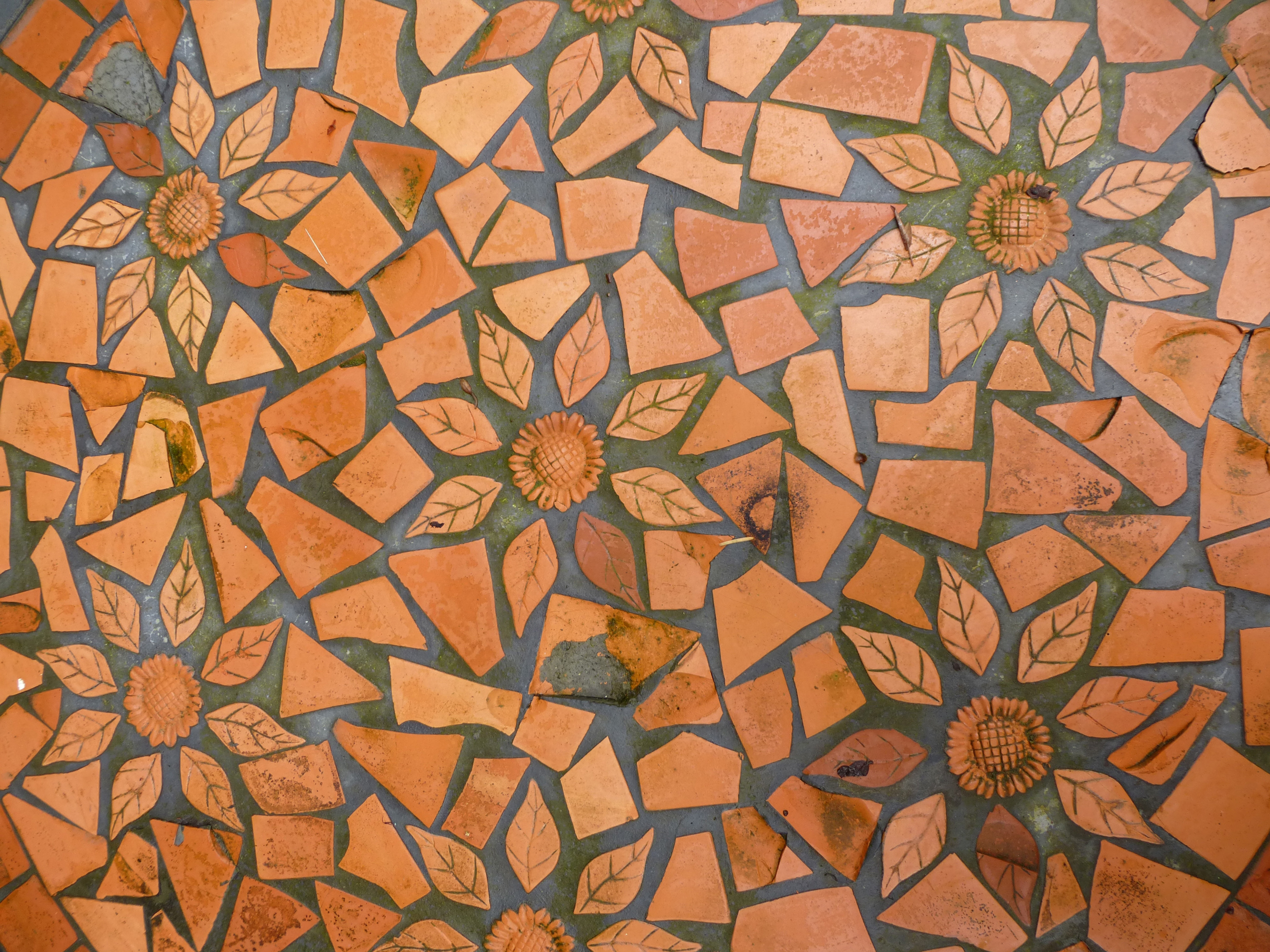 Decorative pavement with floral pattern made of various shapes of terracotta, high-angle close-up