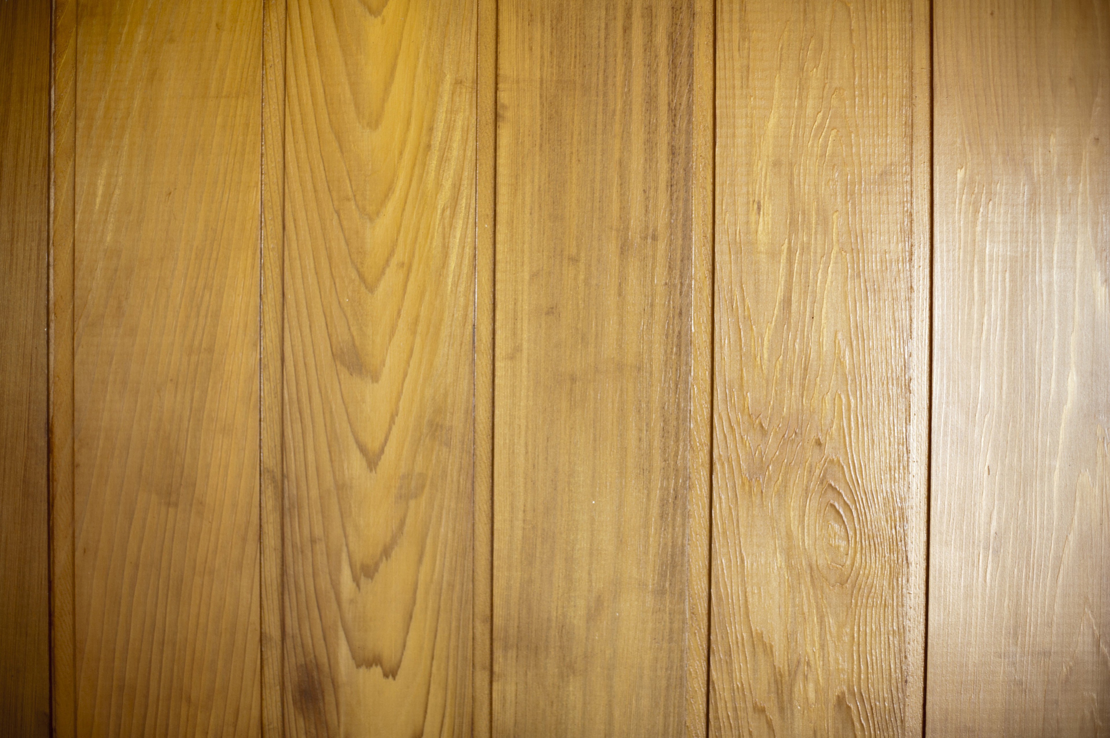 Brown polished wood panelling made of horizontal wall mounted battens, close-up