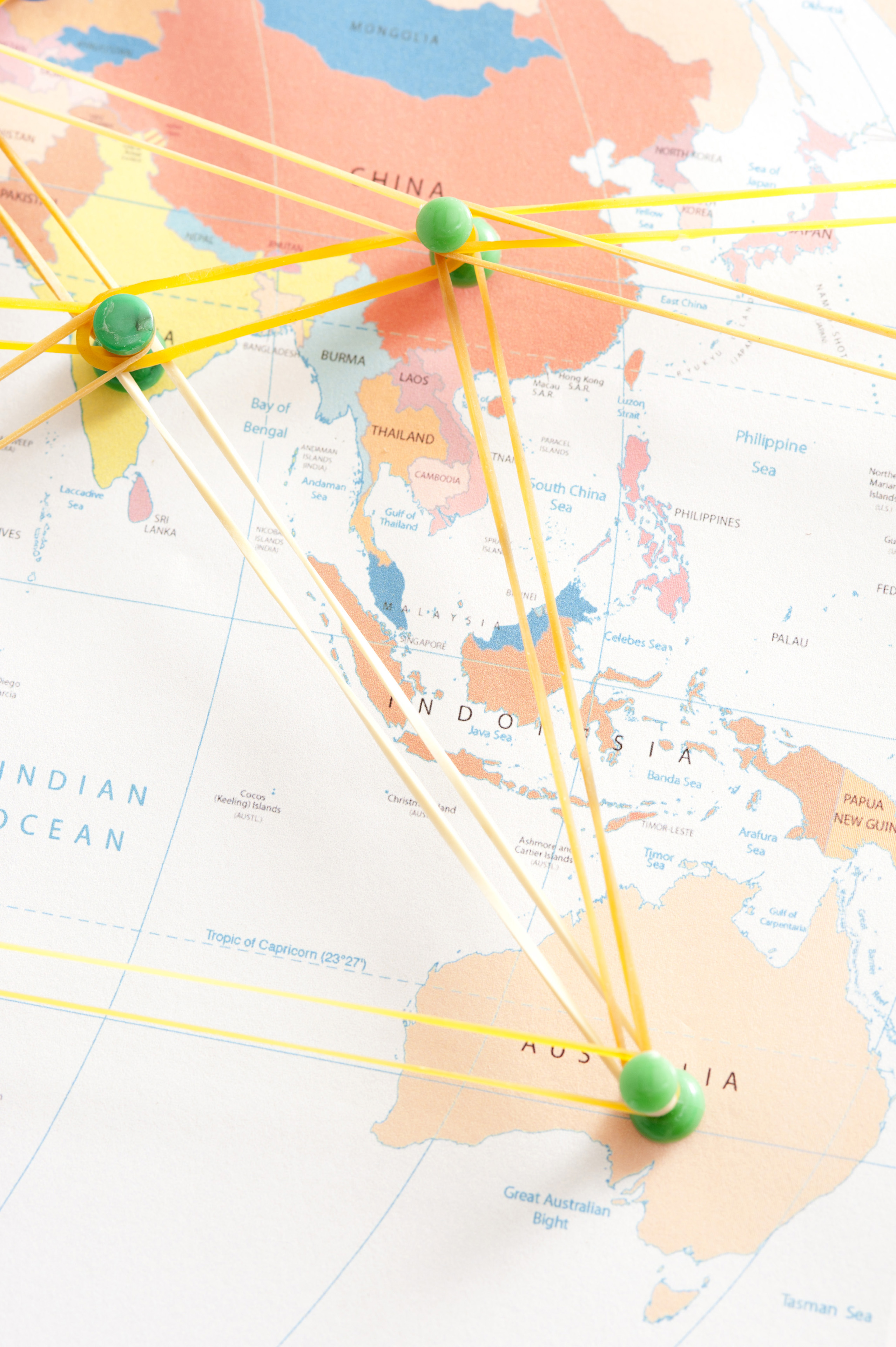 Communications Network Concept Image Illustrated by Pins Inserted in Map of Australasia and Connected by Elastic Rubber Bands