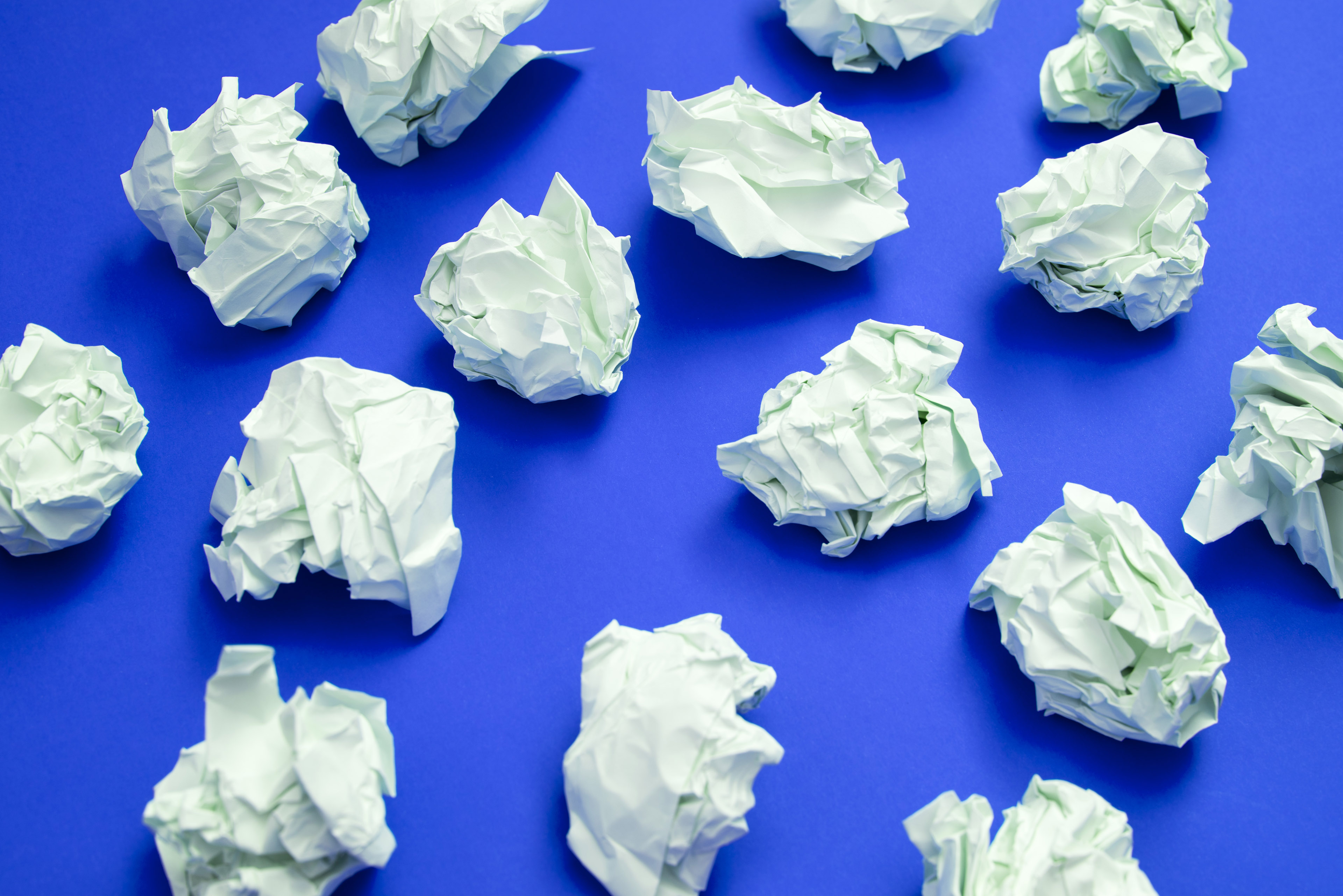 Writers block concept or business impasse with scattered balls of crumpled white paper with discarded ideas on a blue background viewed from above
