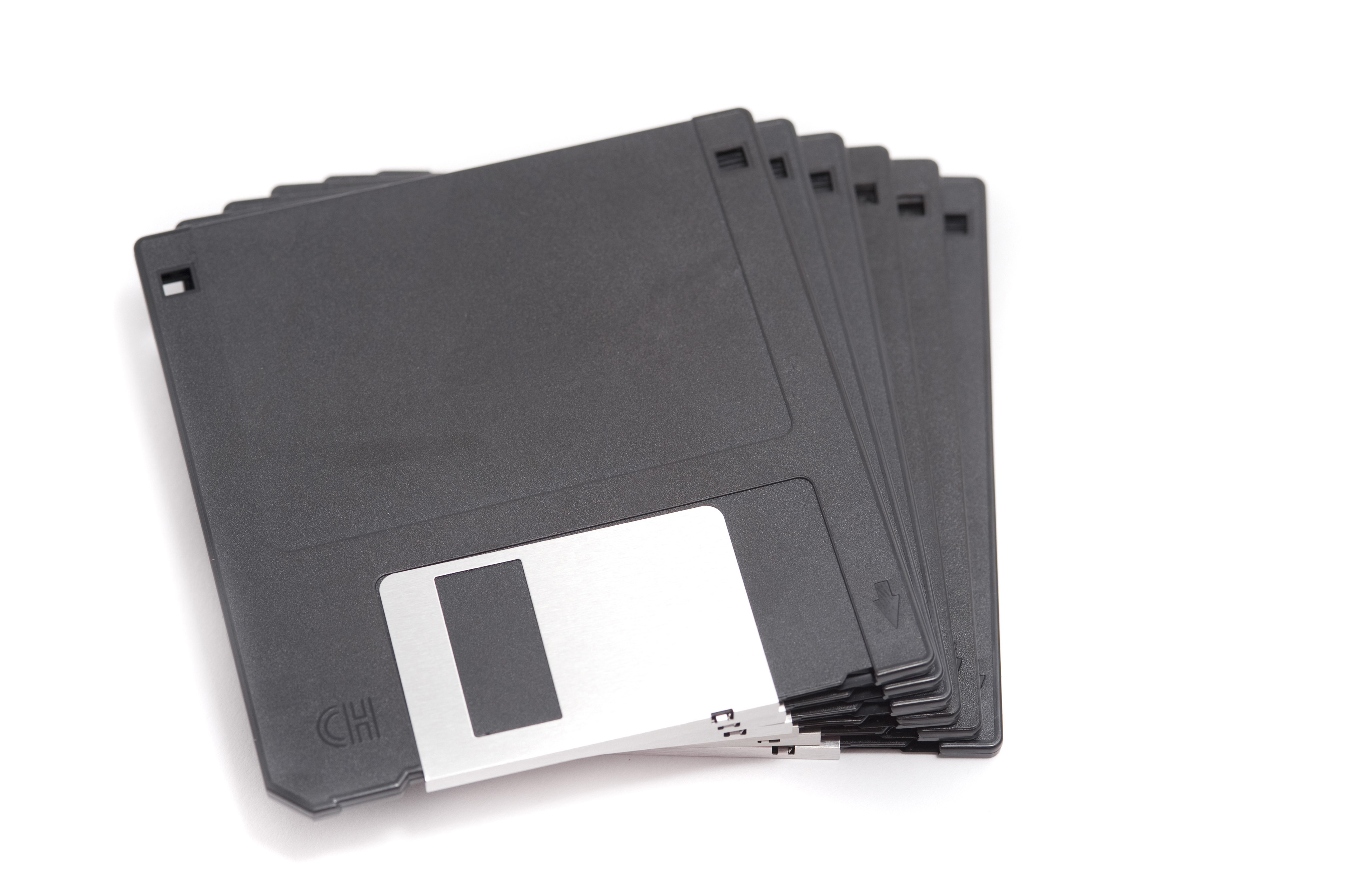 Close up Pile of Gray Computer Diskettes Isolated on White Background.