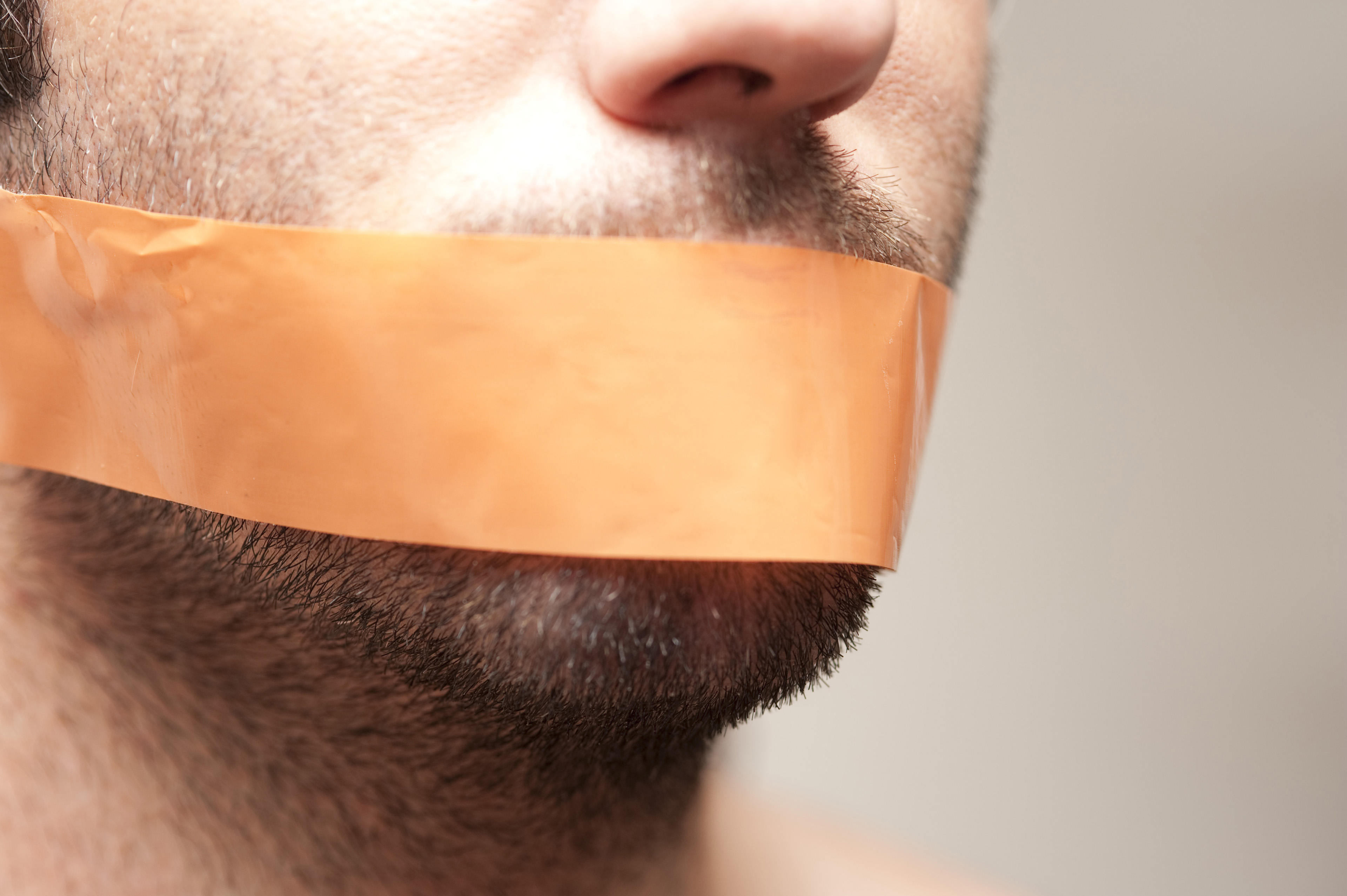 Can't Speak - Close Up of Man with Facial Hair Stubble Gagged with Orange Tape Across Mouth