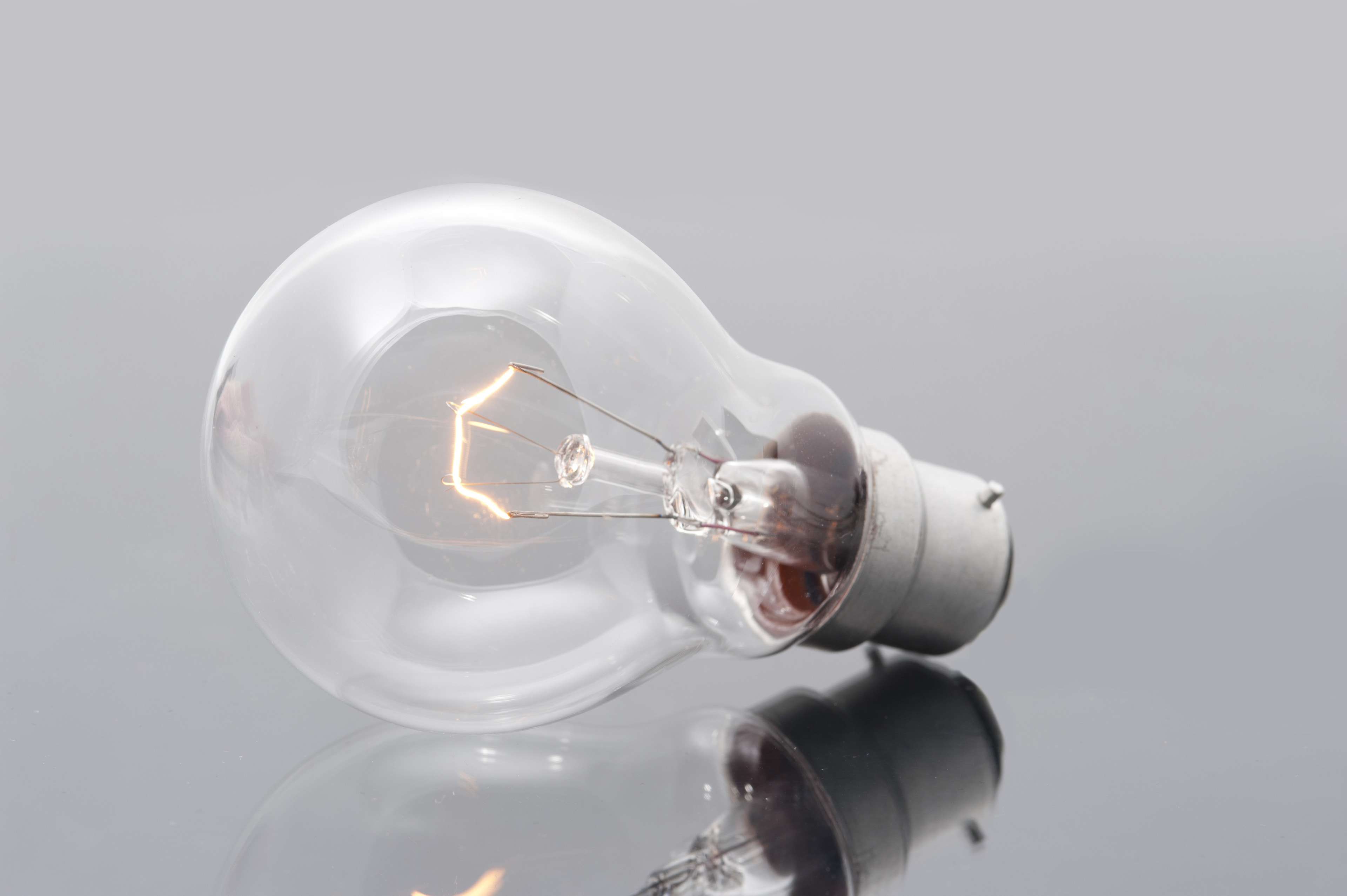 Domestic light bulb with a bayonet fitting and a glowing filament on a reflective grey surface for power and energy or bright ideas concepts