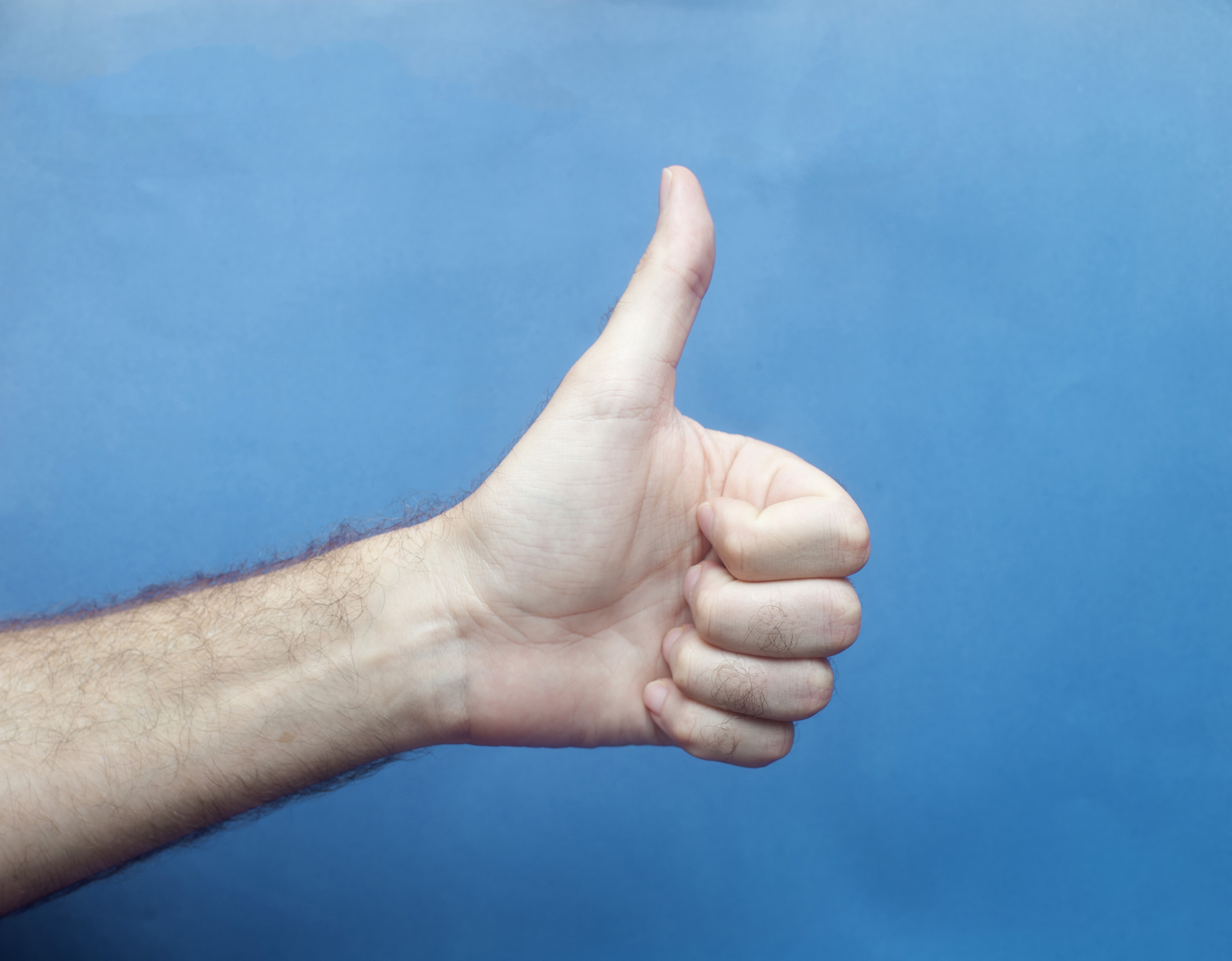 I like this - Male Hand Giving Thumbs Up Sign Giving Approval with Blue Background