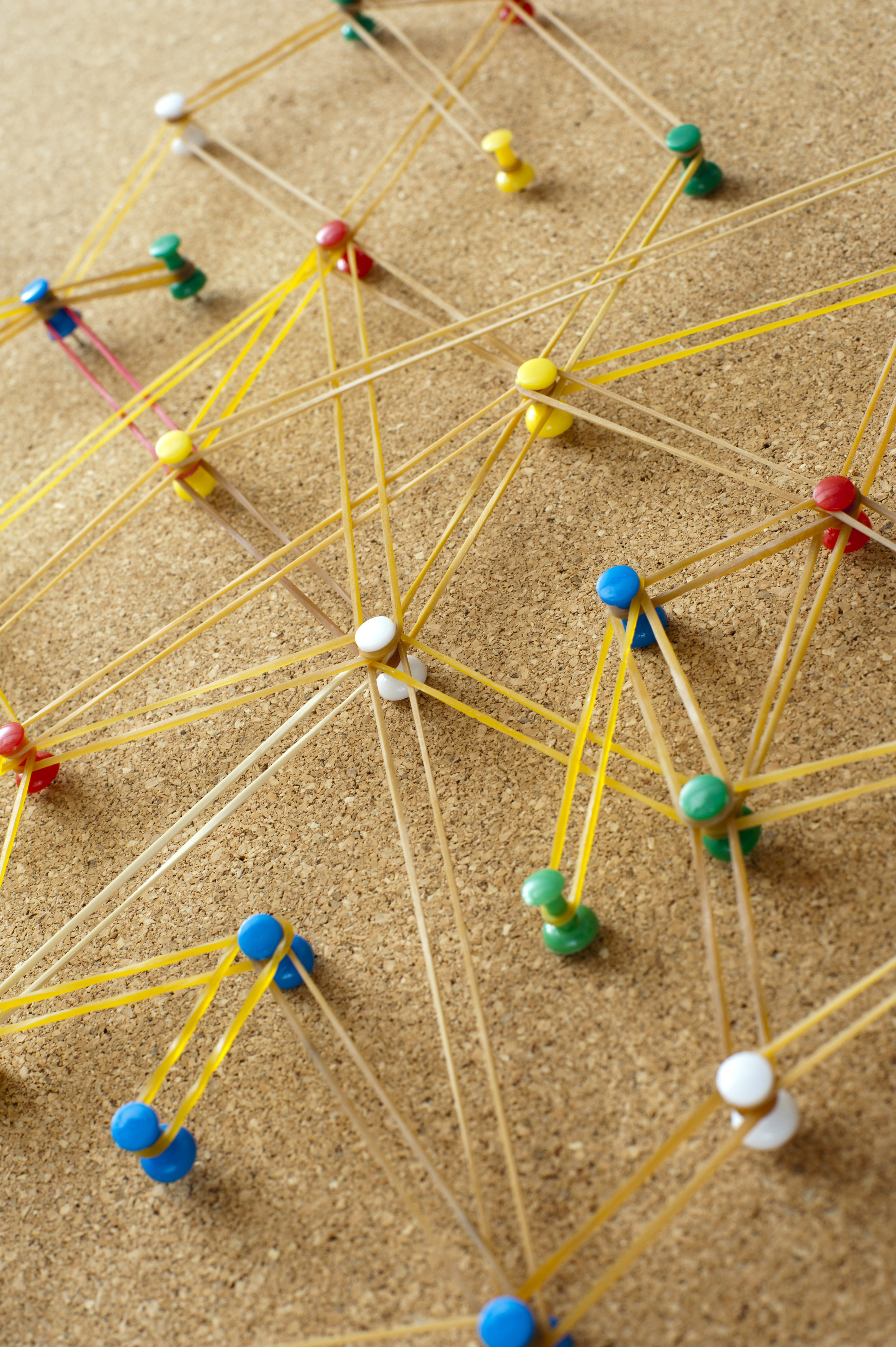 Networking concept formed from rubber bands connecting bright colorful pins on a cork board
