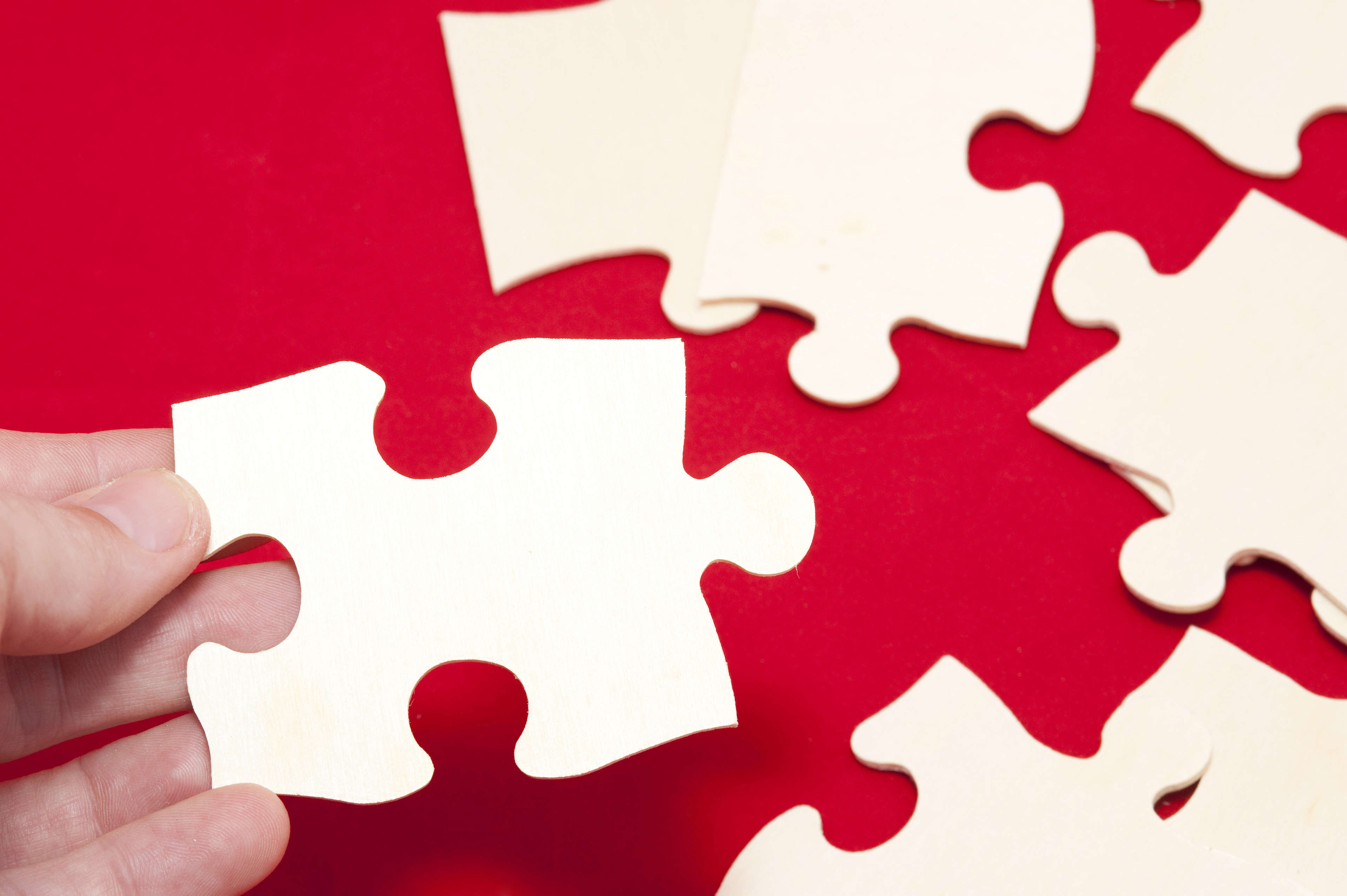 Close Up of Hand Assembling Blank Puzzle Pieces on Red Surface, Business Teamwork Concept Image
