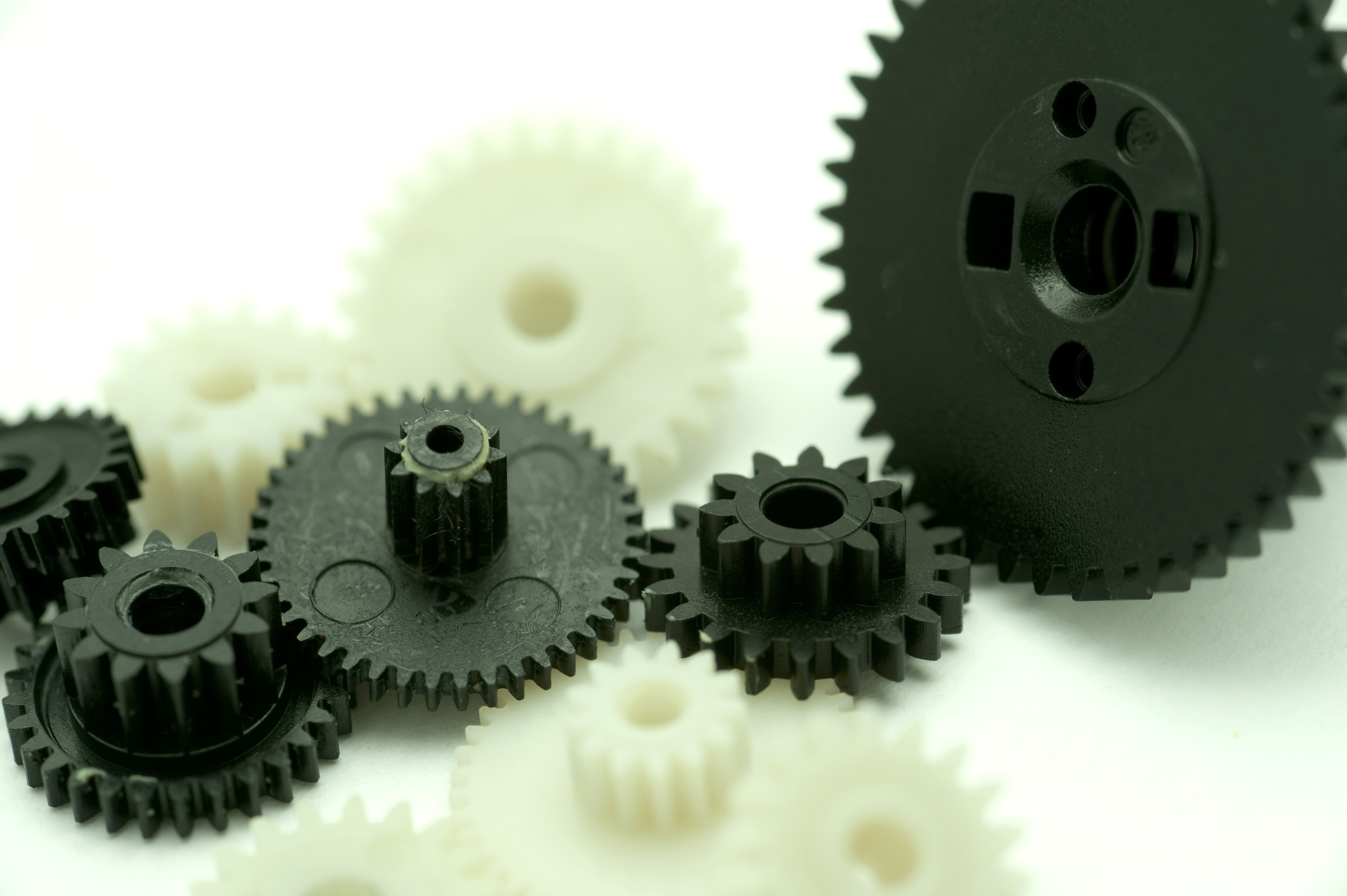 Close up Assorted Sizes of Plastic Black and White Gear Wheels on White Background, Emphasizing Teamwork Concept