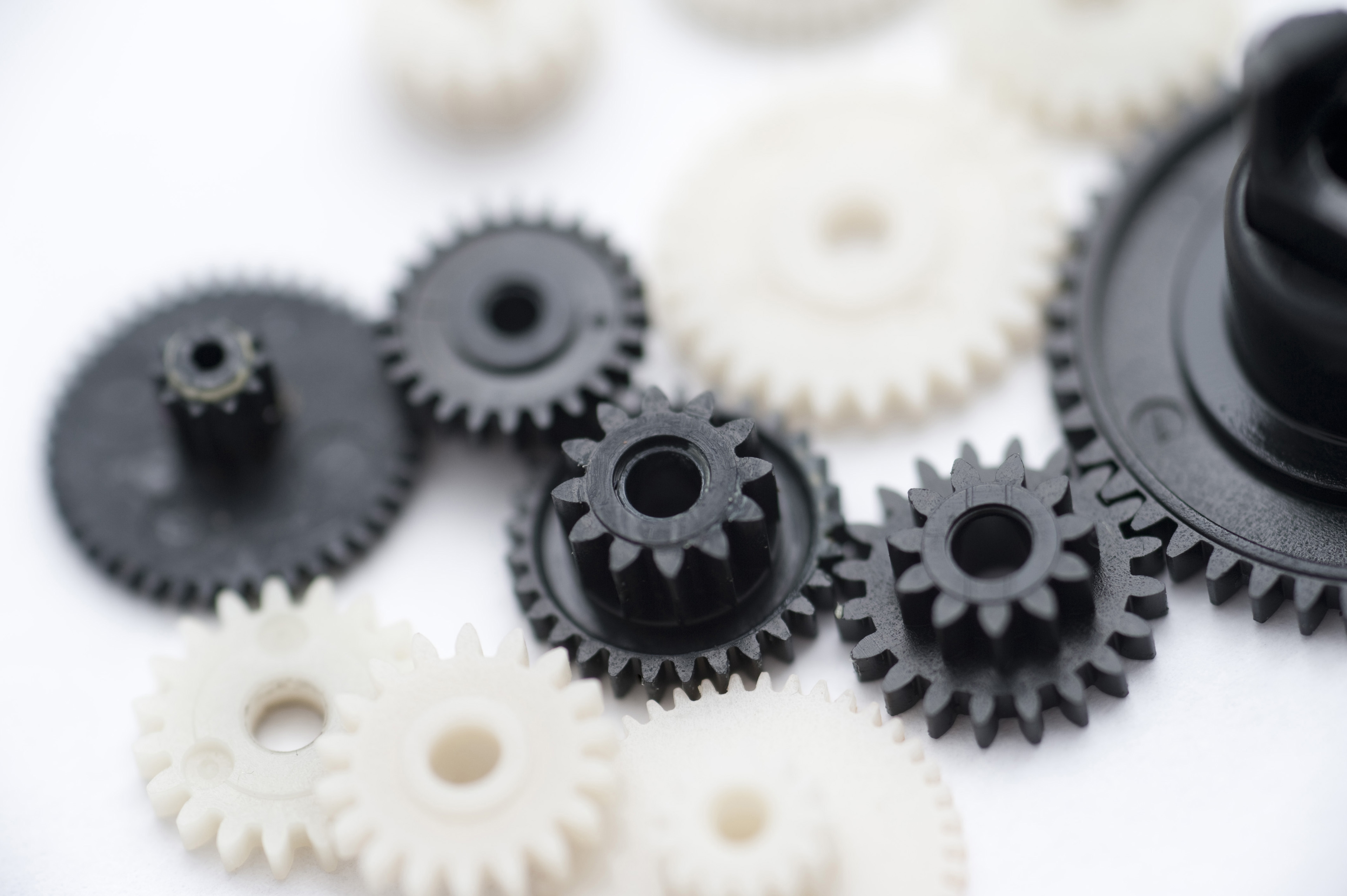 Close Up of Various Sized Black and White Plastic Gears on White Background, Business Teamwork Concept Image