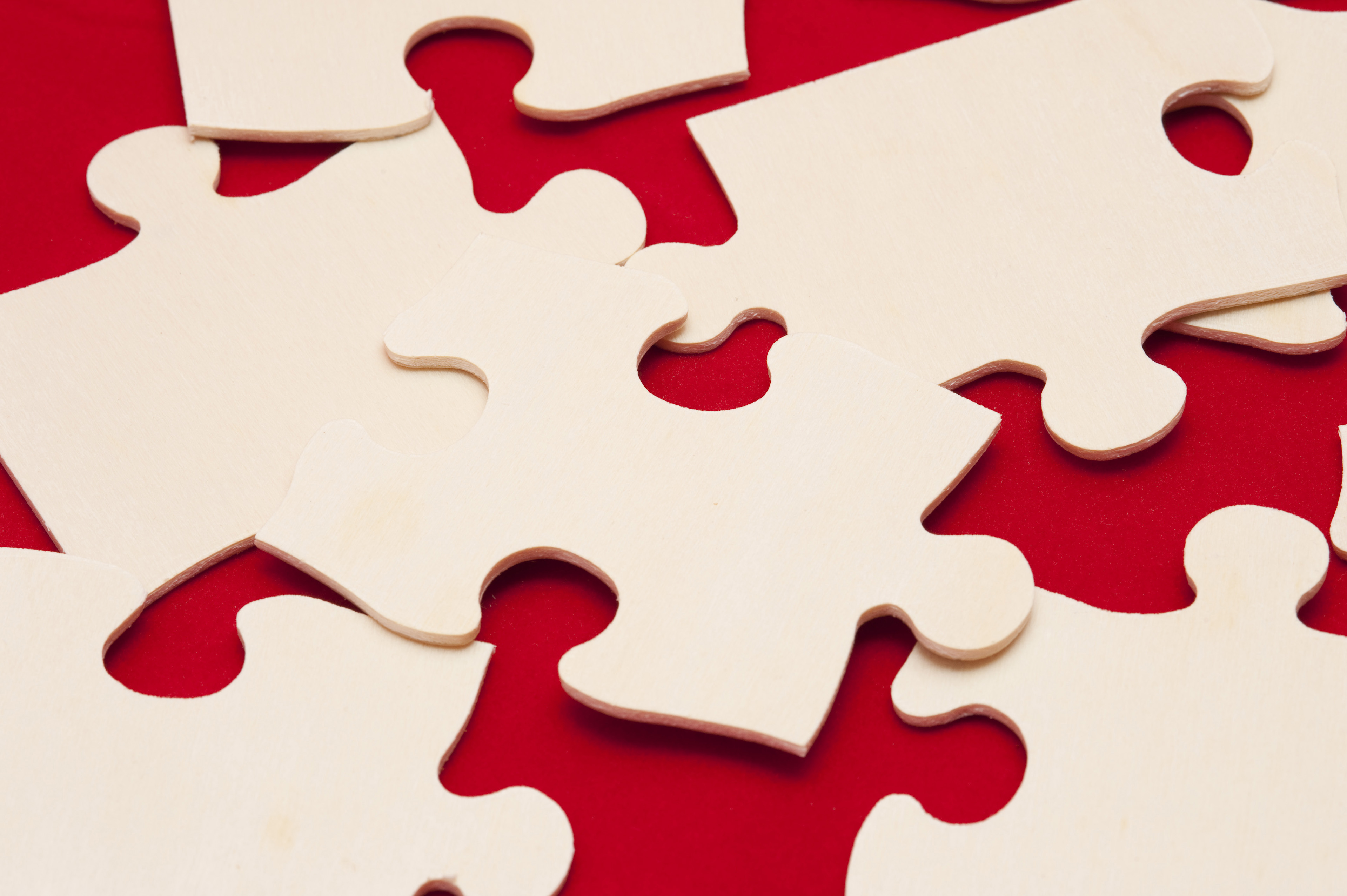Close up Shot of Conceptual White Jigsaw Puzzle Pieces on Red Background