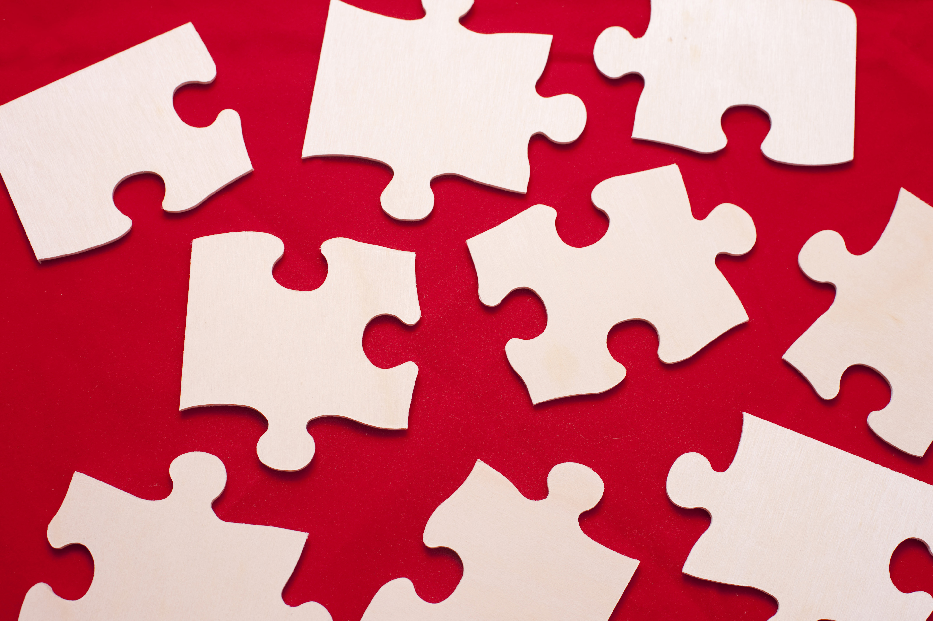Overhead view of a group of differently shaped scattered white puzzle pieces on a red background in a problem solving concept