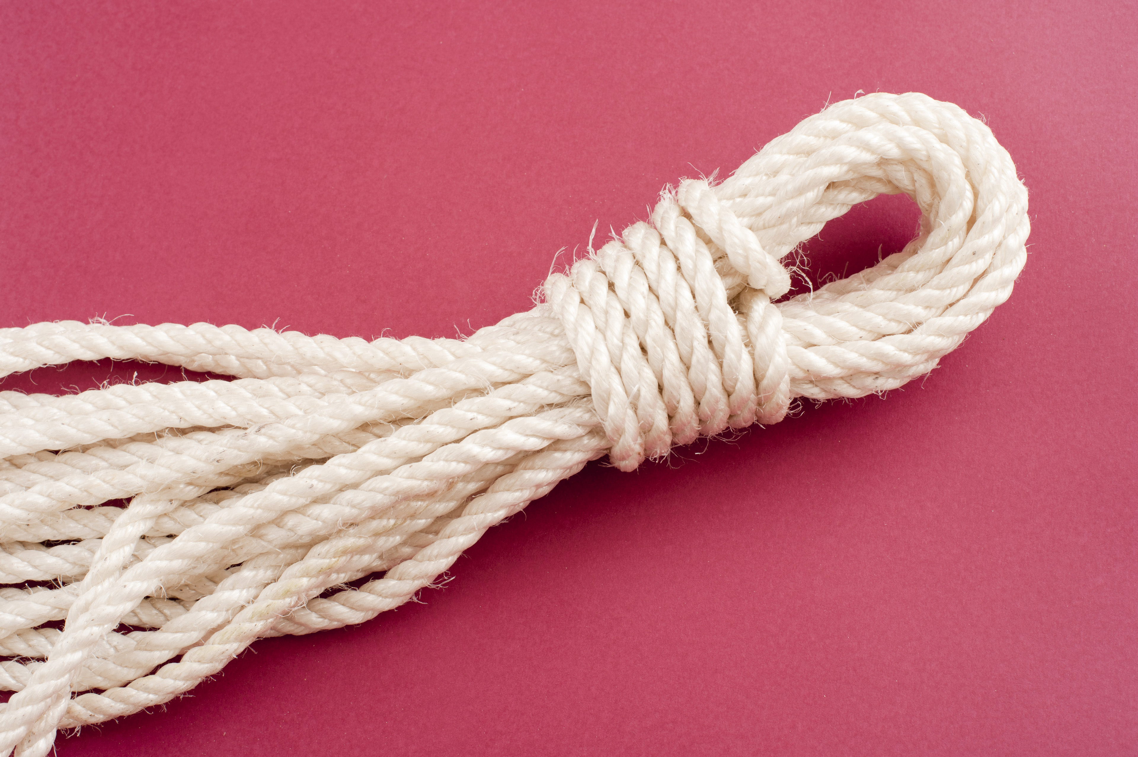 Neatly coiled and tied length of clean new white rope on a red background with copyspace