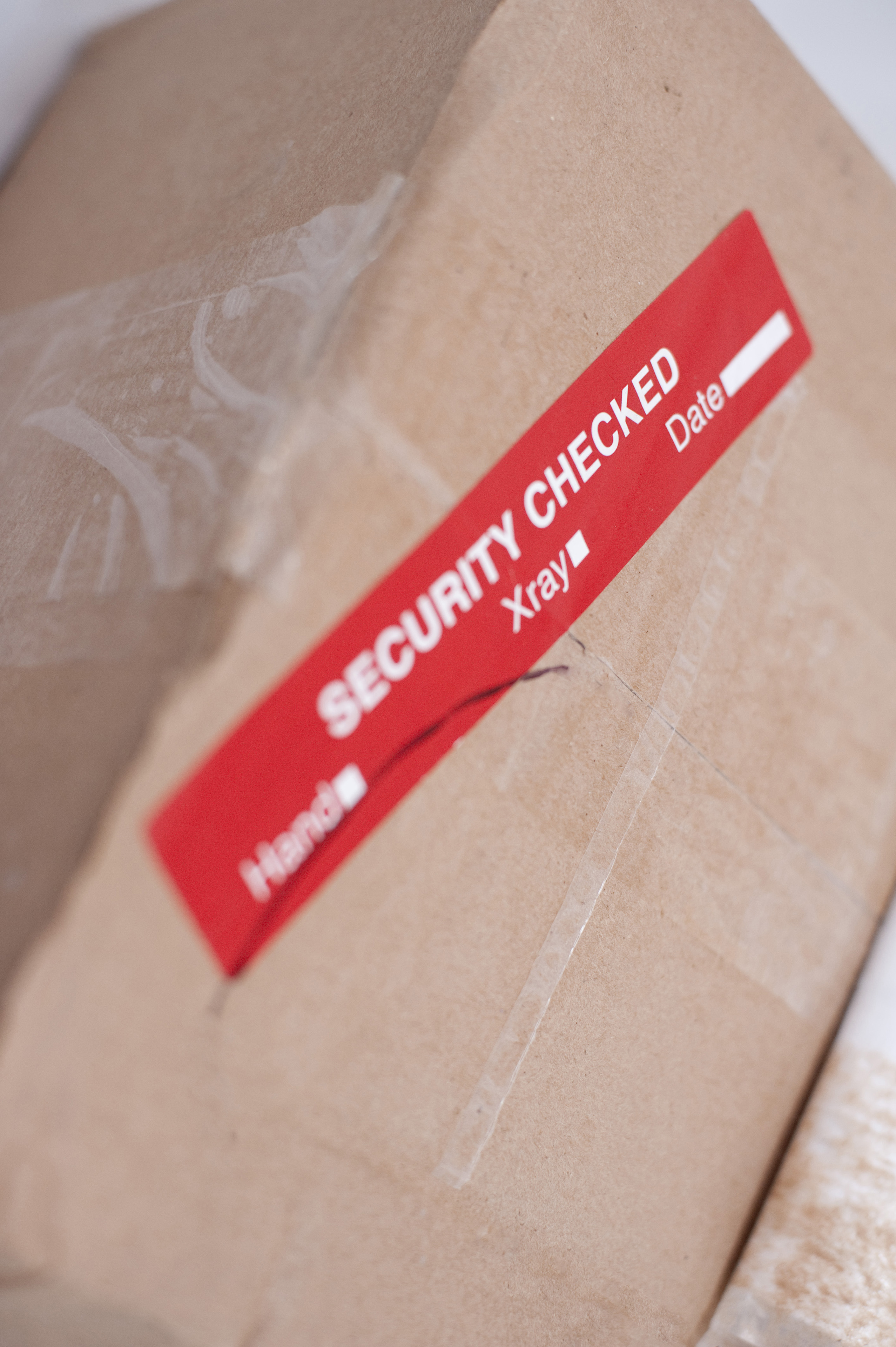 Close up Brown Cardboard Box with Red Security Label Sticker.