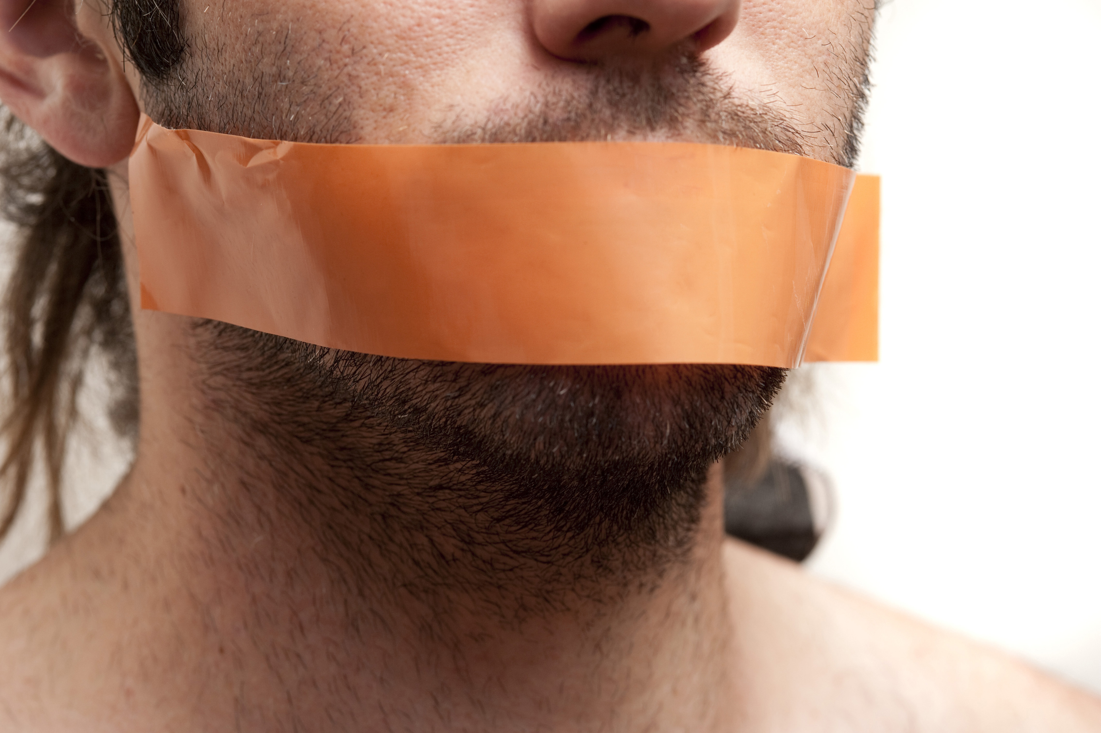 Close up Young Man with Beard and Mustache Putting a Brown Tape Over his Mouth for Silence Concept, Isolated on White Background.