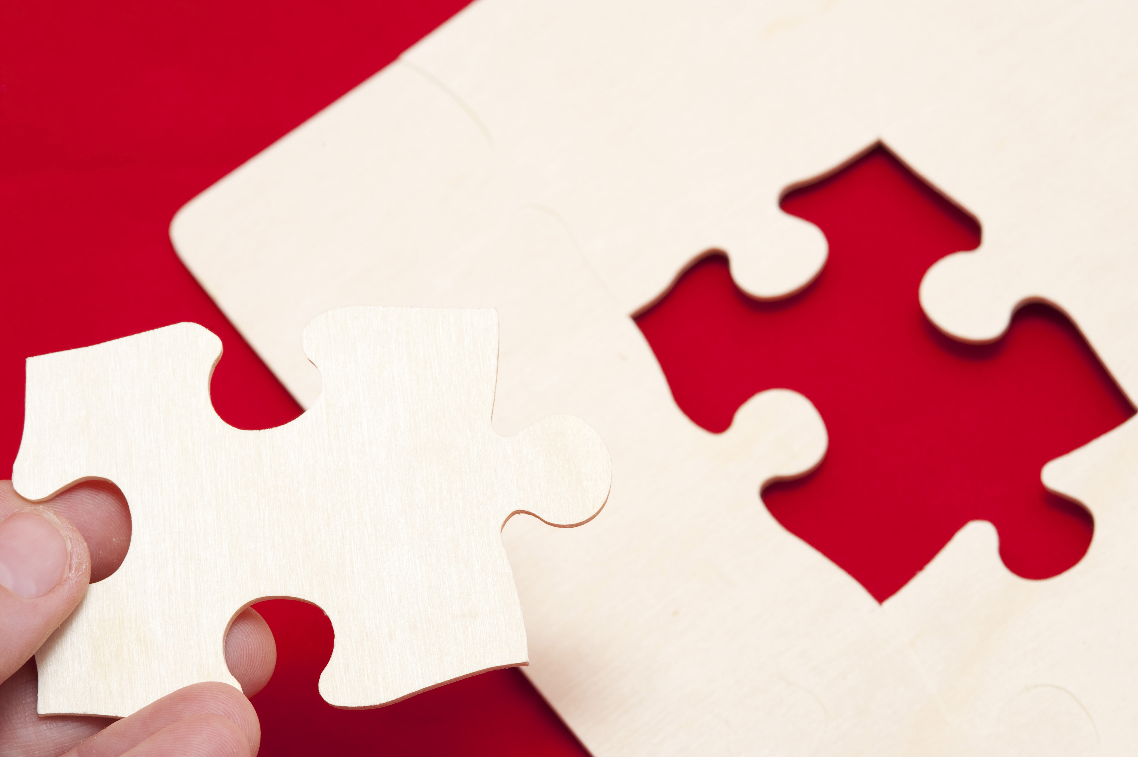 Conceptual Man Holding White Puzzle Piece to Complete the Puzzle on the Red Table
