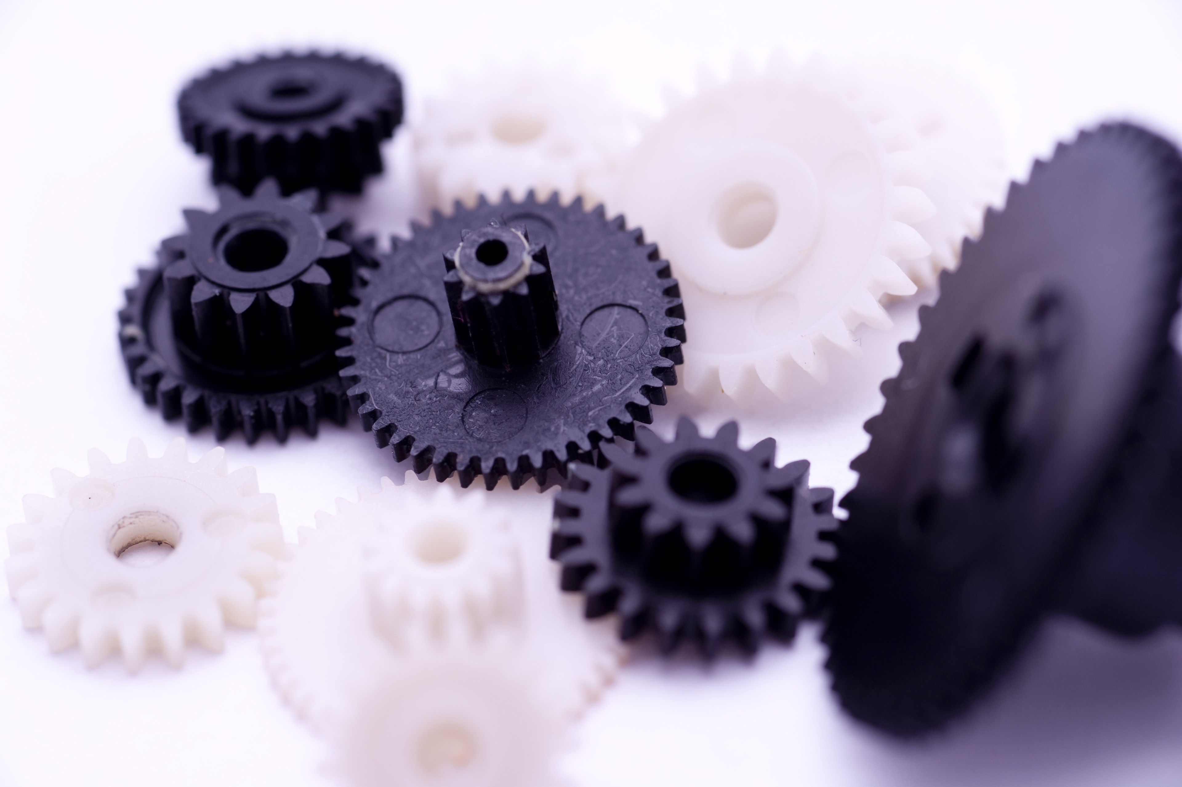 Team Work Concept - Close up Black and White Gears on White Background.