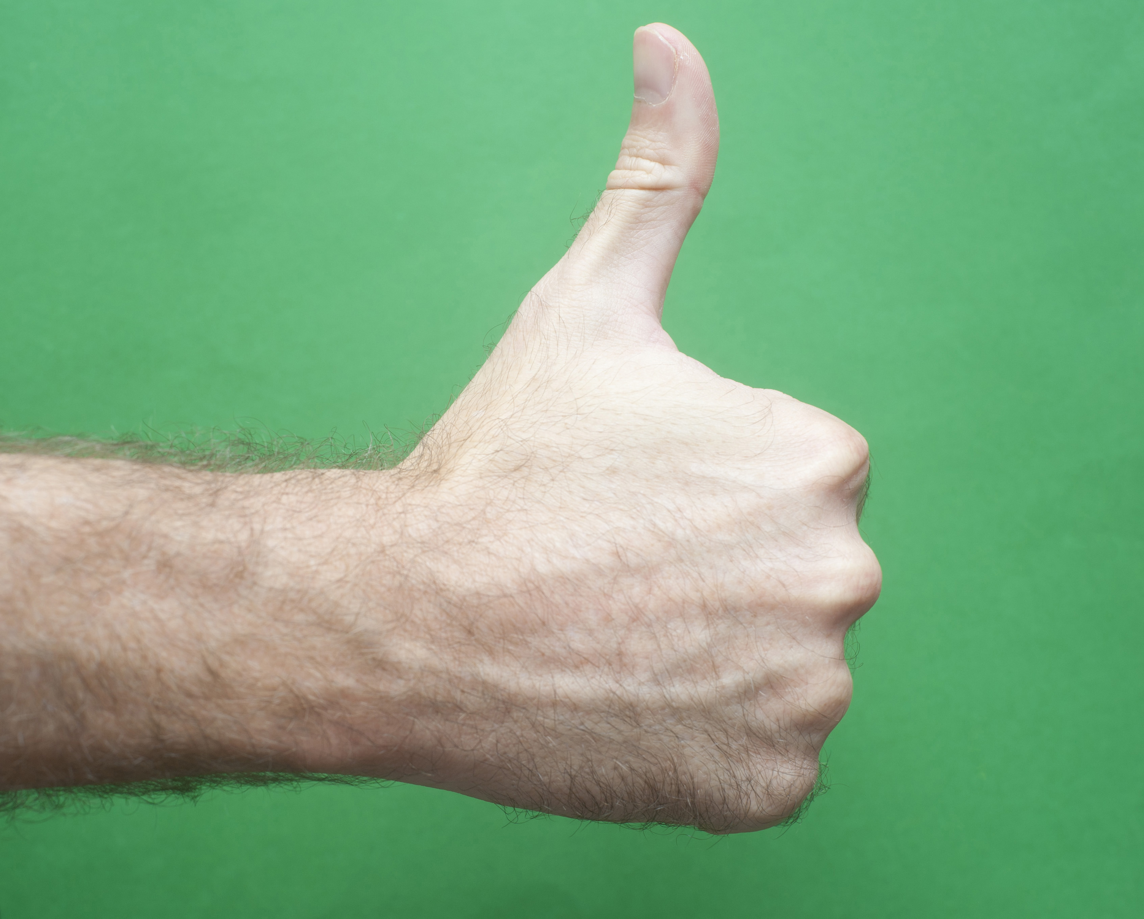 Close up Bare Hairy Man Hand Showing Thumbs Up Sign, Isolated on Green Background.