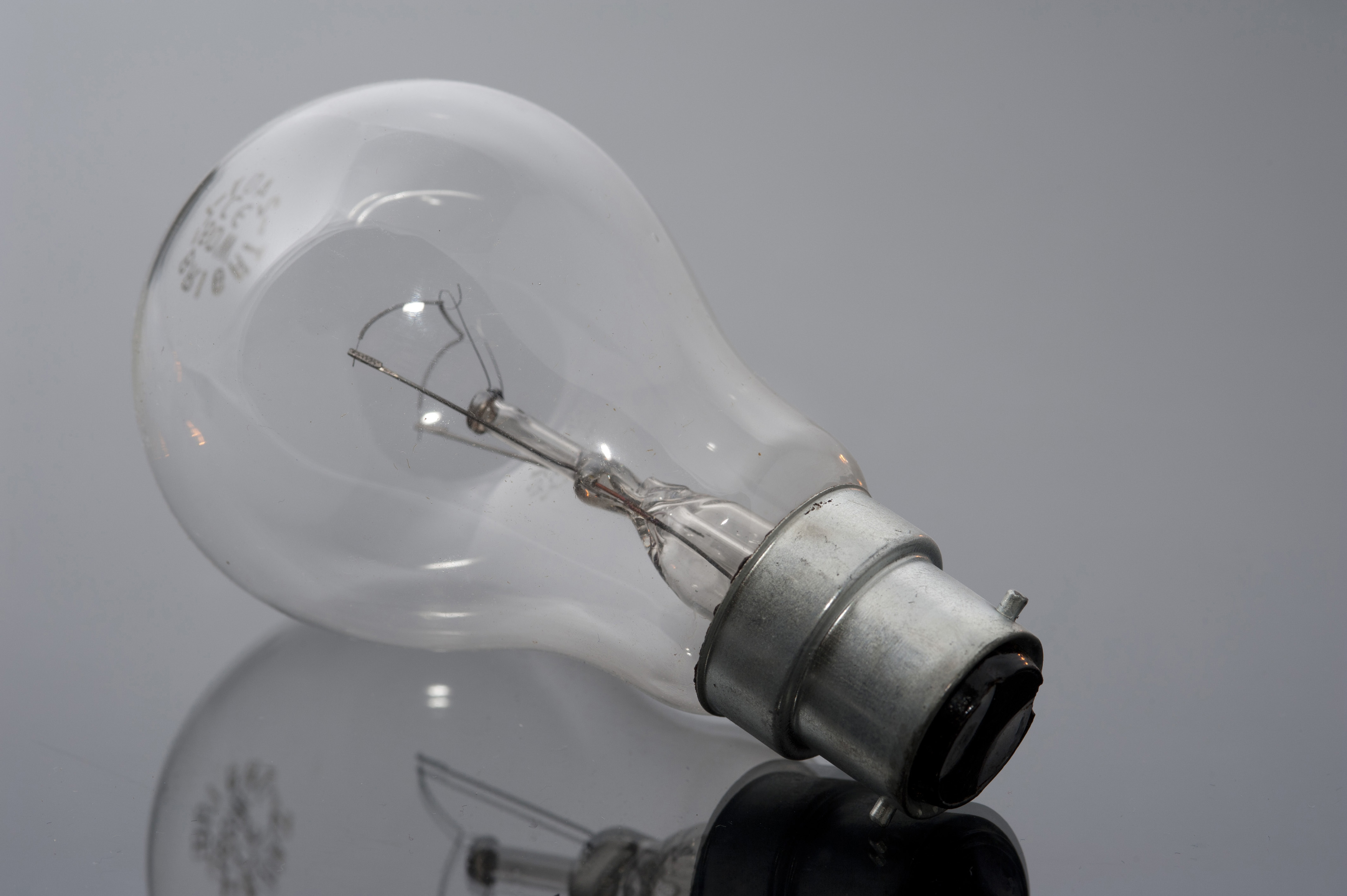 Close up Shot of Conceptual Unlit Bulb on Glossy Gray Table, Emphasizing its Reflection.