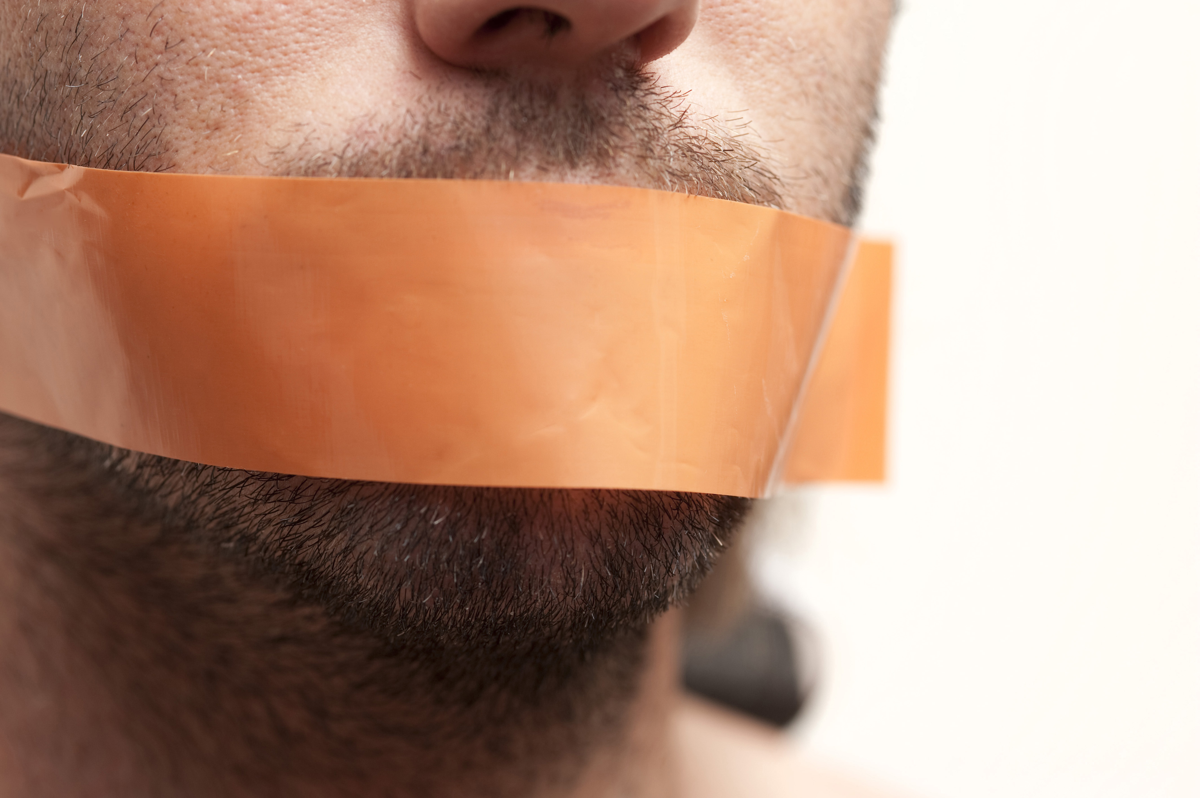 Censor and Freedom of Speech Concept - Close up Man Face with Brown Tape Covering his Mouth.