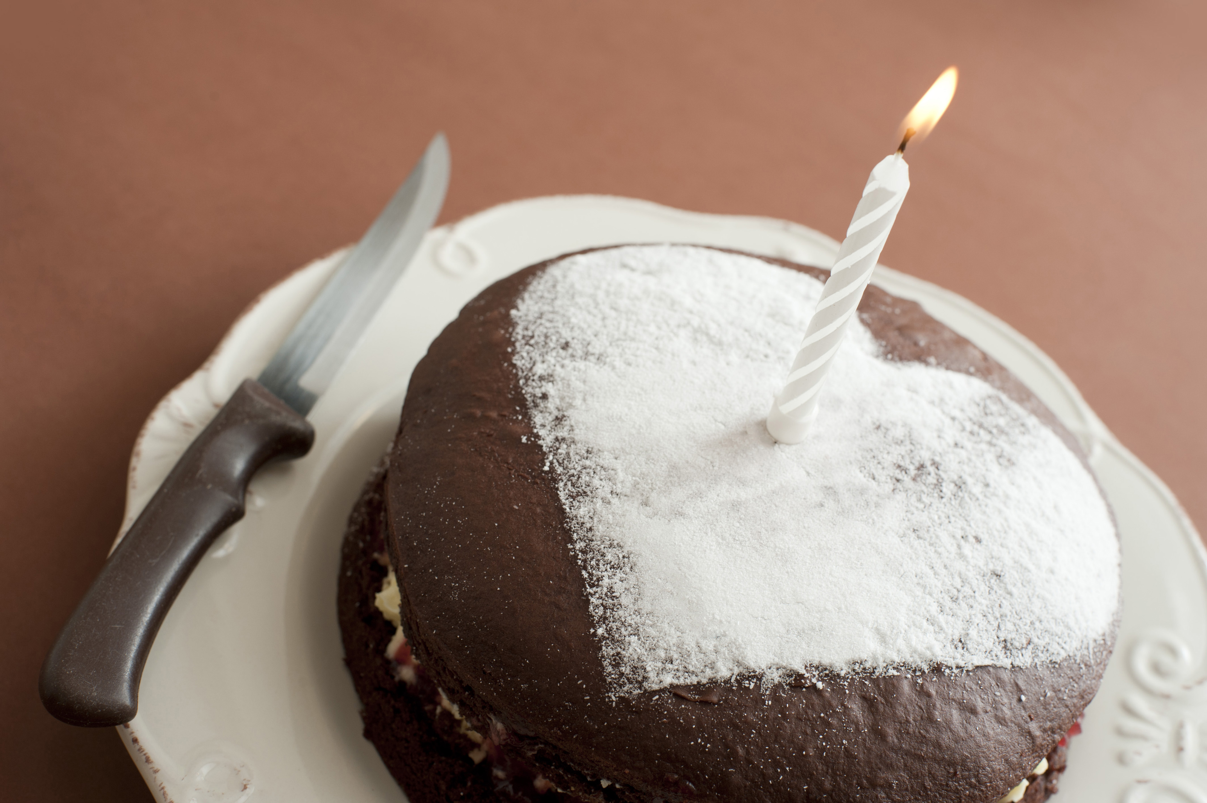 Homemade birthday chocolate cake topped with a vanilla heart shape and a burning candle, celebrating one year
