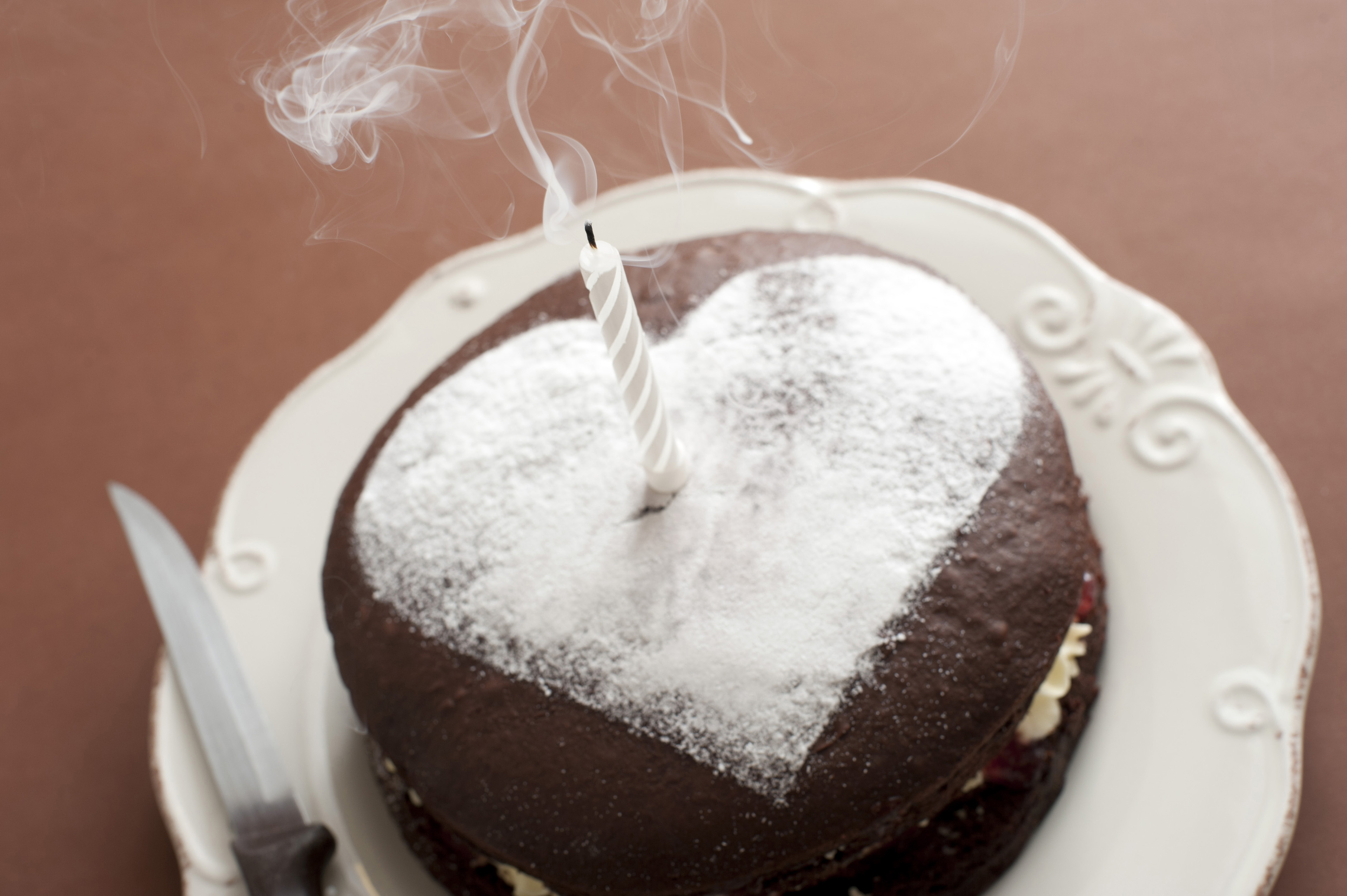 A chocolate birthday cake for a loved one with a white icing sugar heart shape on top and a single extinguished candle