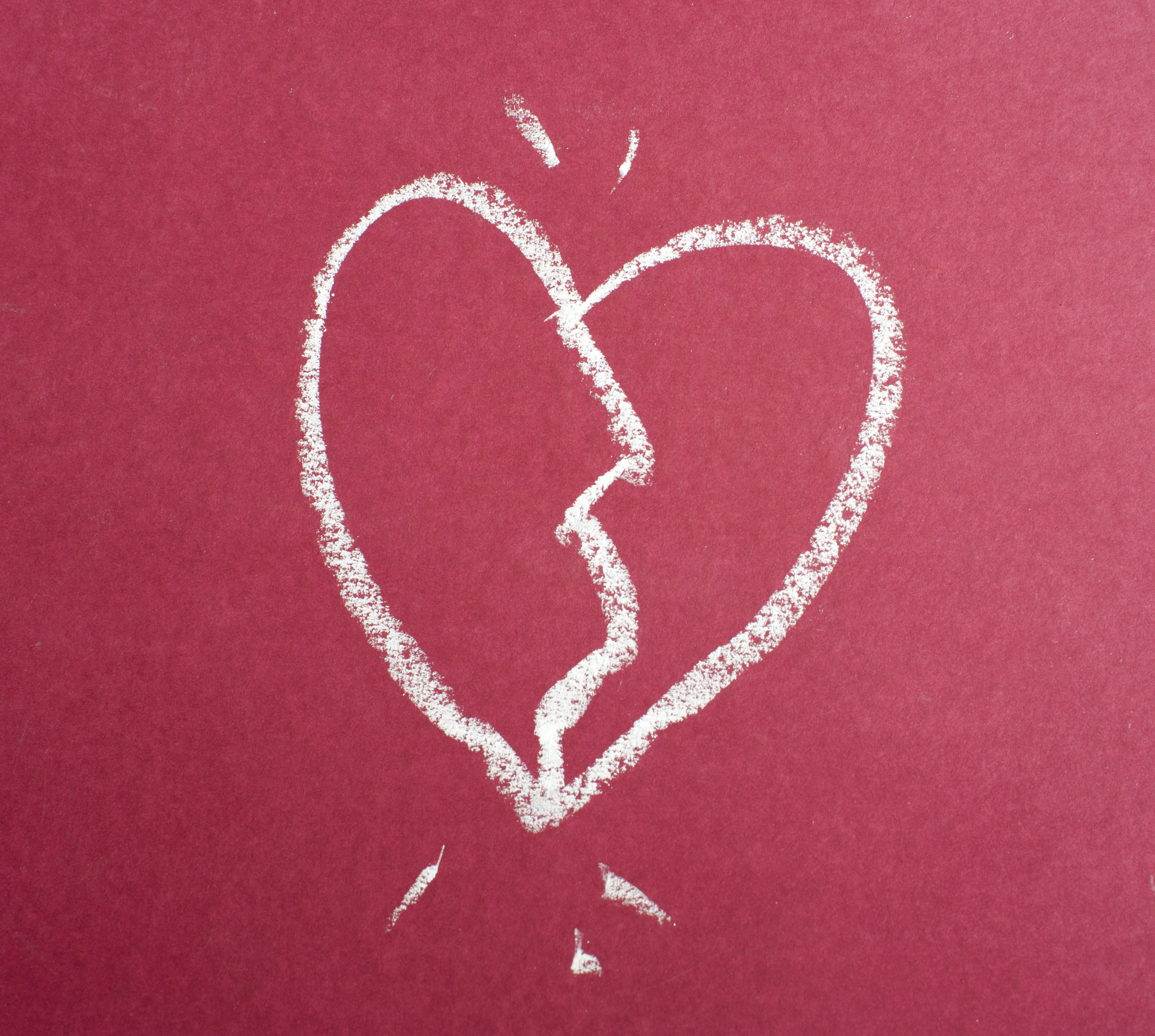 A sketched broken love heart hand drawn with white chalk on a red chalkboard.
