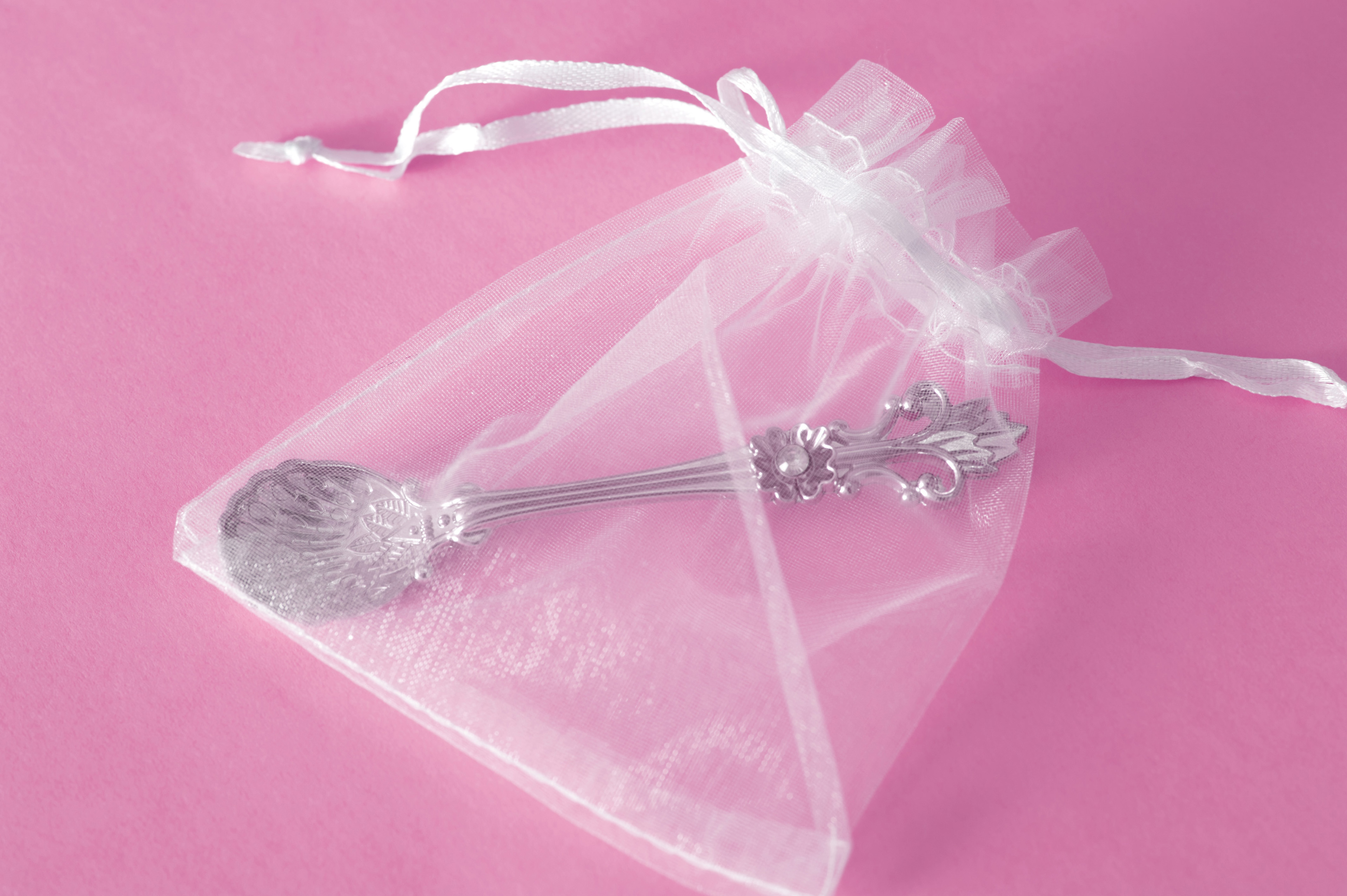 Christening Giveaway Concept - Close up Small Silver Spoon in a See Through Bag. Isolated on Pink Background.