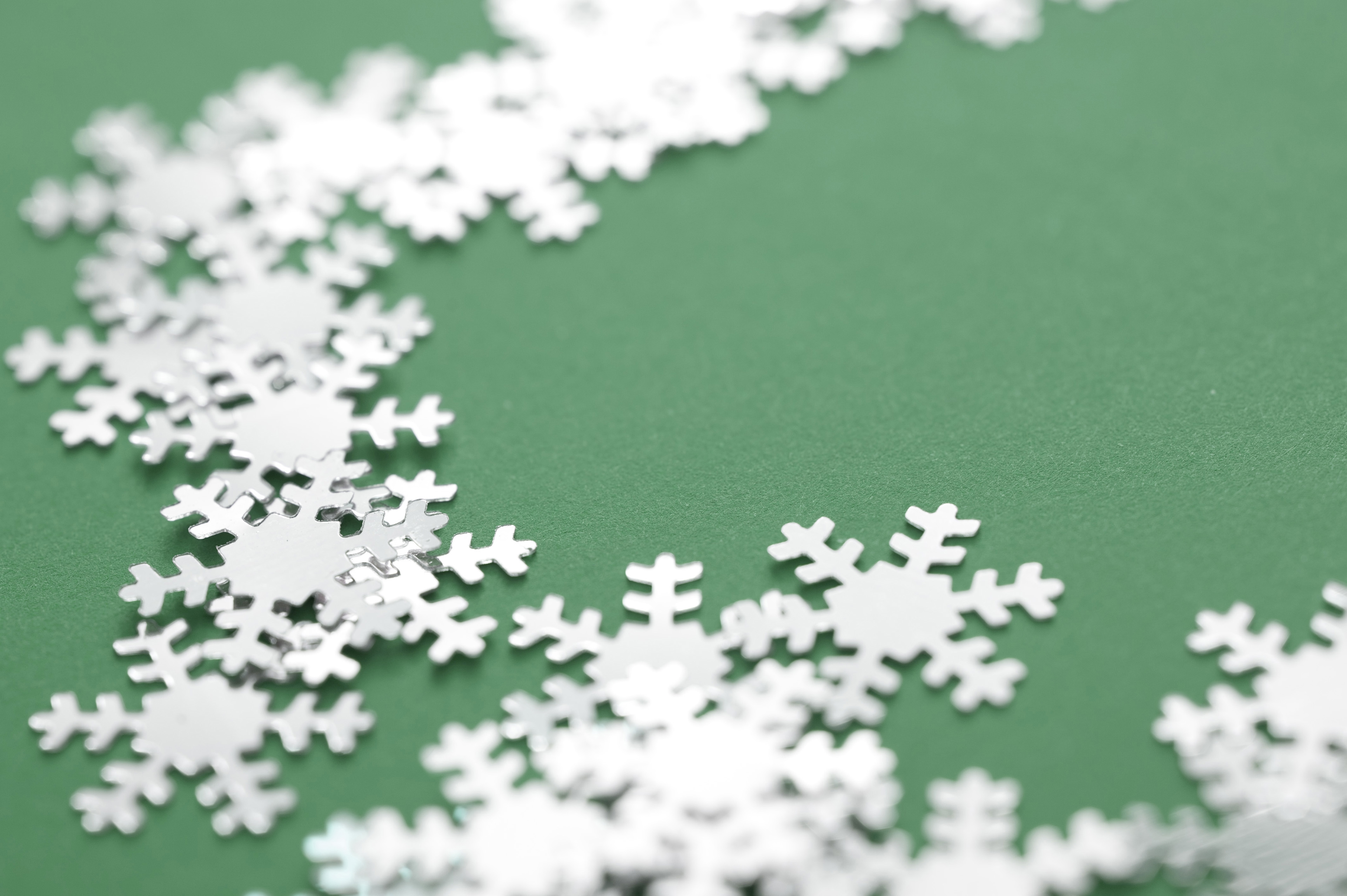 Christmas background of winter snowflakes winding across a green background with shallow dof to the centre and copyspace for your seasonal greeting