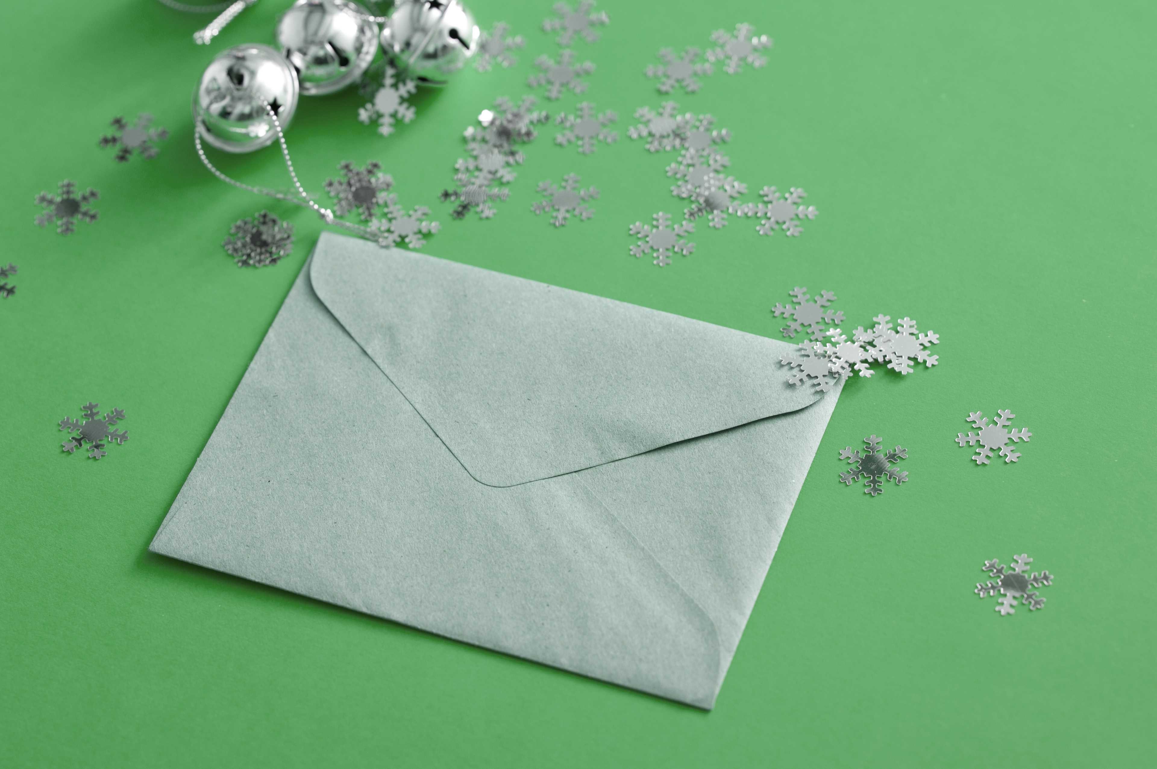Green sealed Christmas letter and decorations with scattered snowflakes and silver bells on a green background for festive correspondence