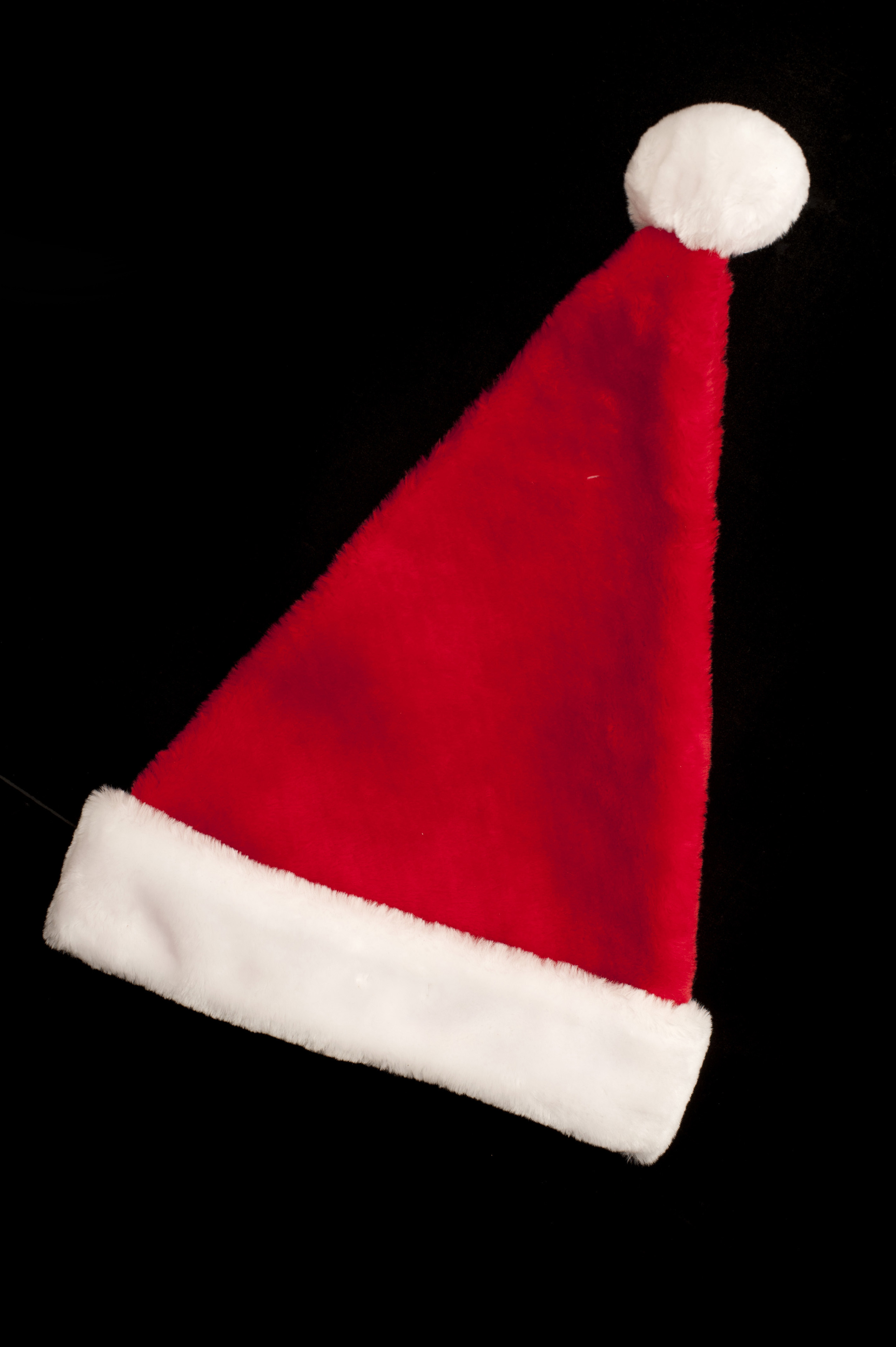 Festive red Christmas Santa hat lying diagonally on a black in vertical format for a holiday background or card