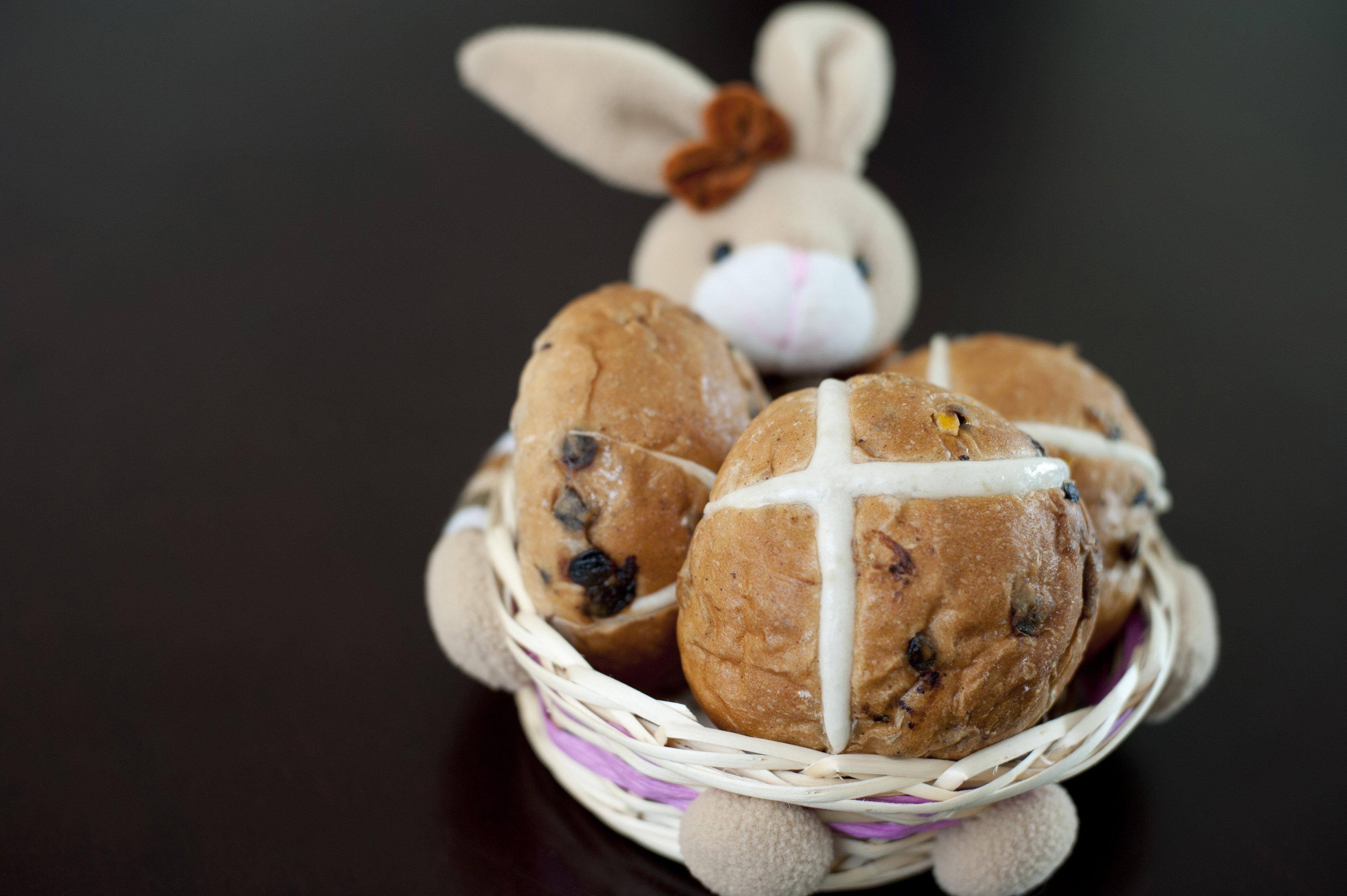 Easter baking concept with delicious fresh fruity Hot Cross Buns displayed by an Easter Bunny in a basket