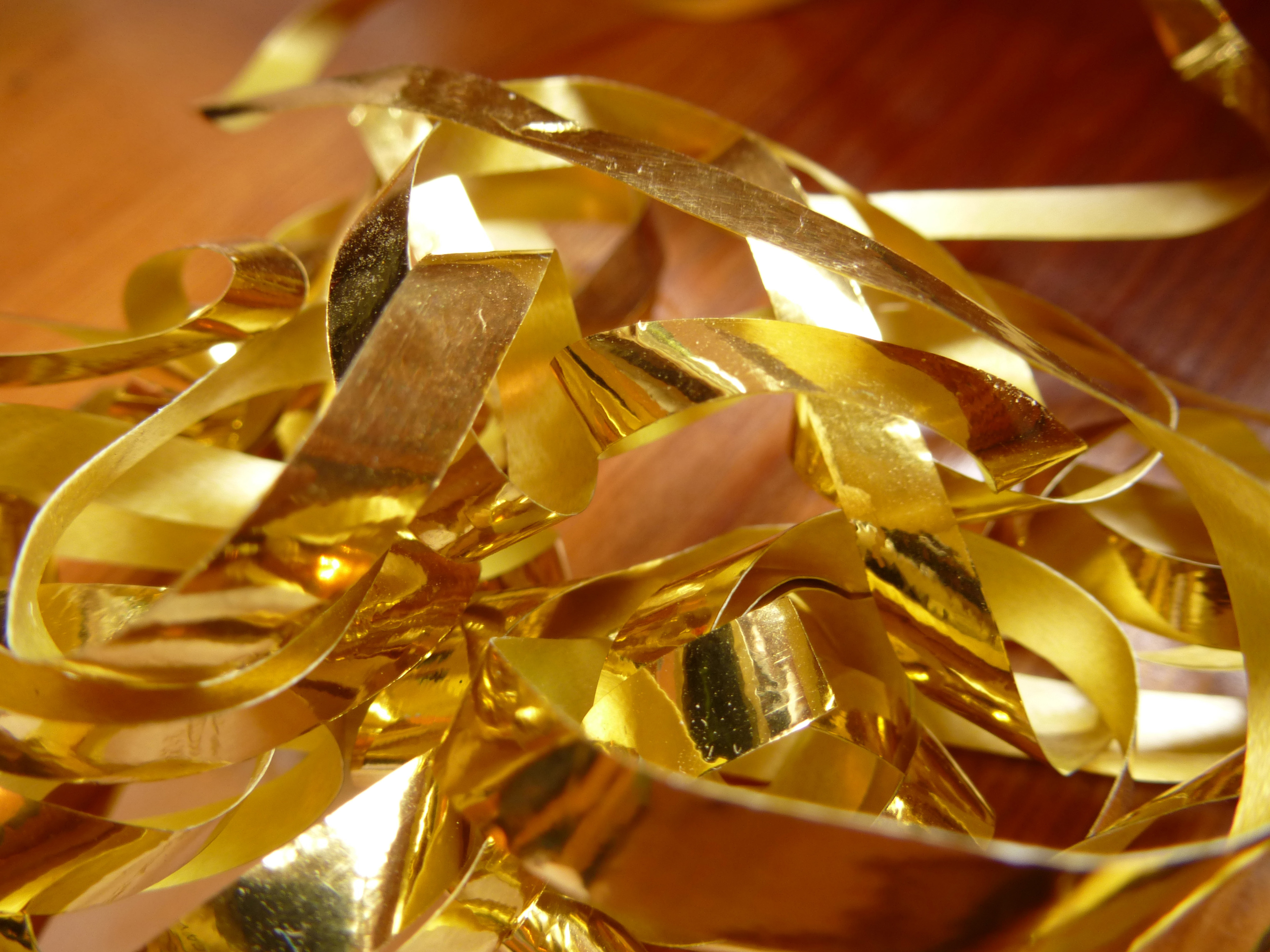 Close up Tangled Gold Foil Cuttings on Top of Wooden Table