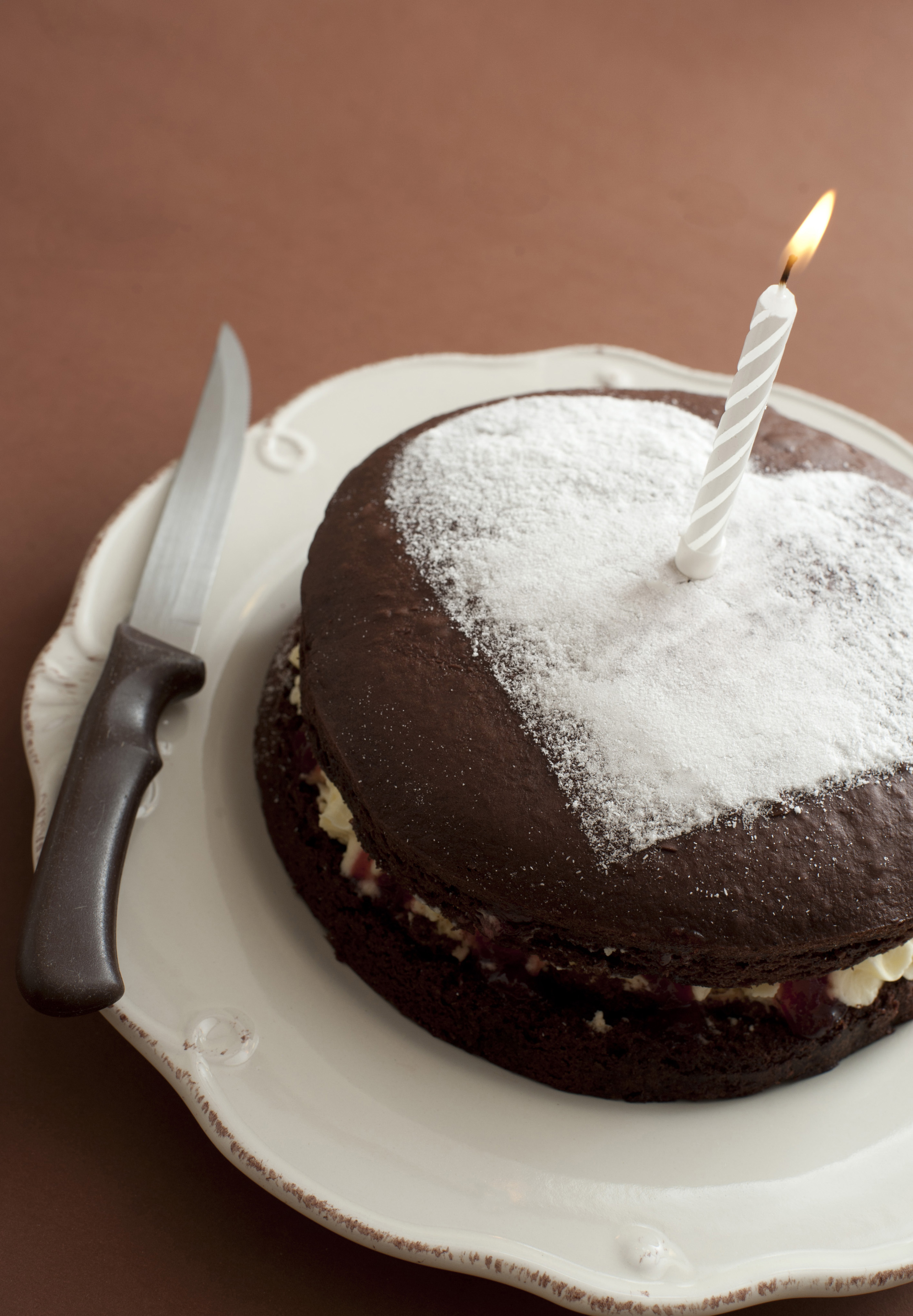 First anniversary cake with an icing sugar heart and single burning candle in a love and romance concept