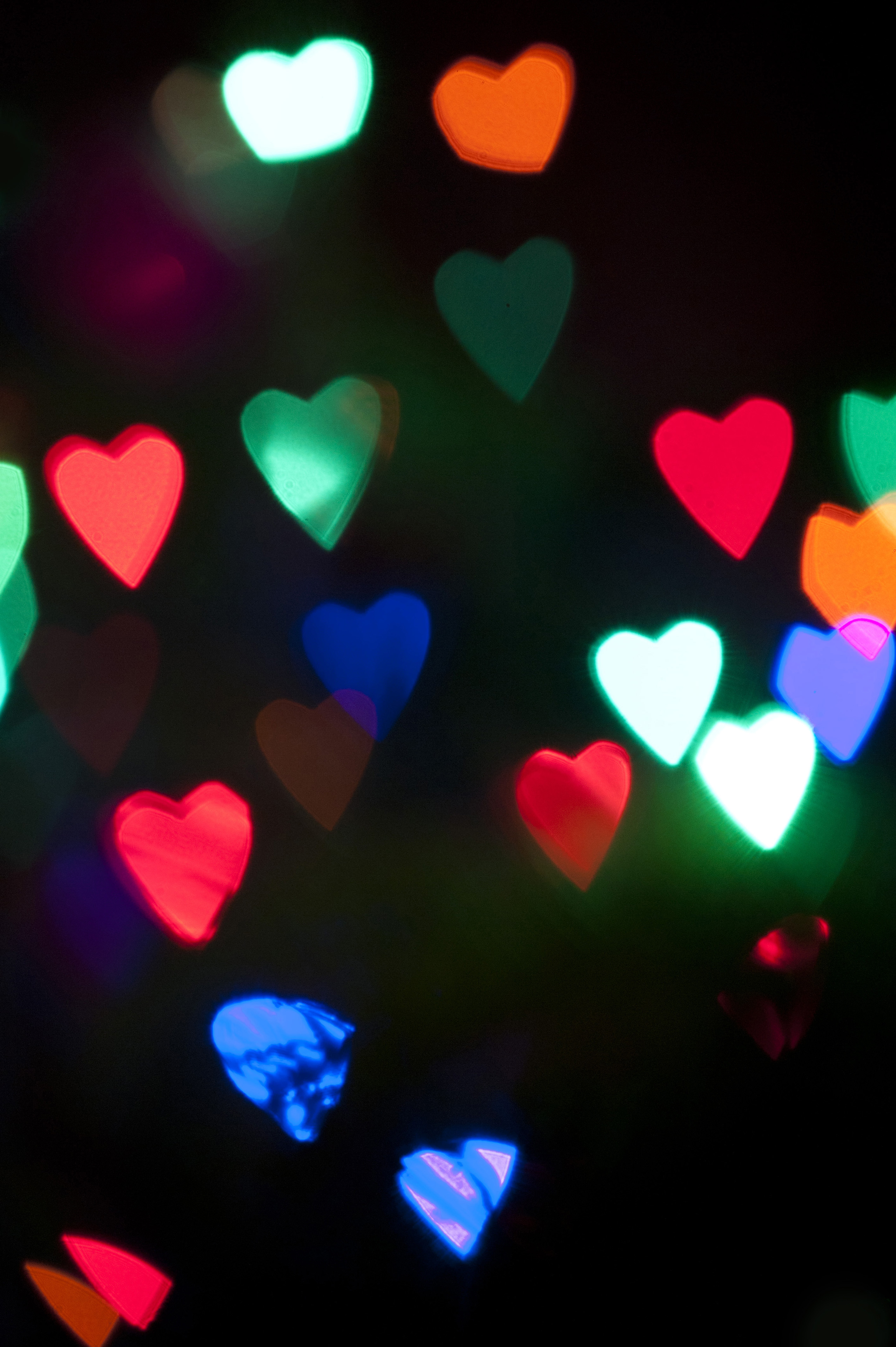 Background of colorful heart-shaped party lights glowing in the darkness at a special event, wedding or Christmas