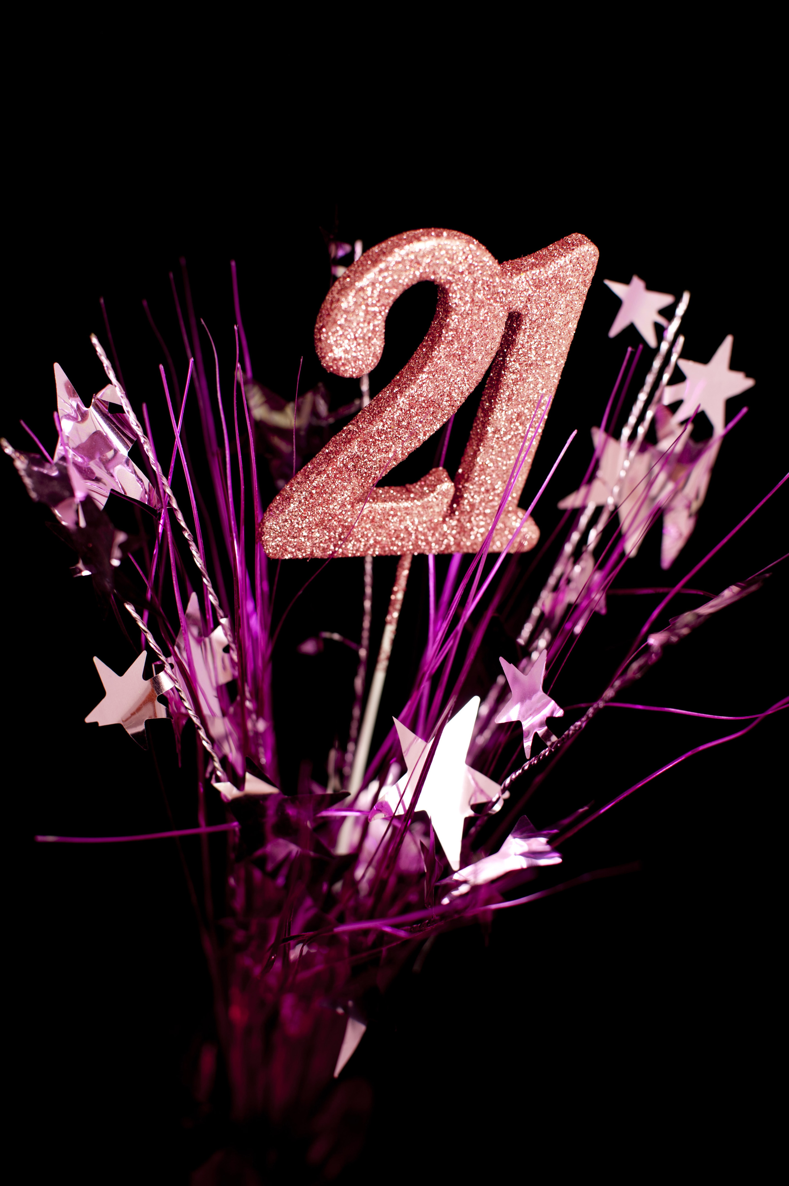 Girls 21st birthday celebrations to mark her coming of age with pink glitter numbers surrounded by a spray of stars over a dark background