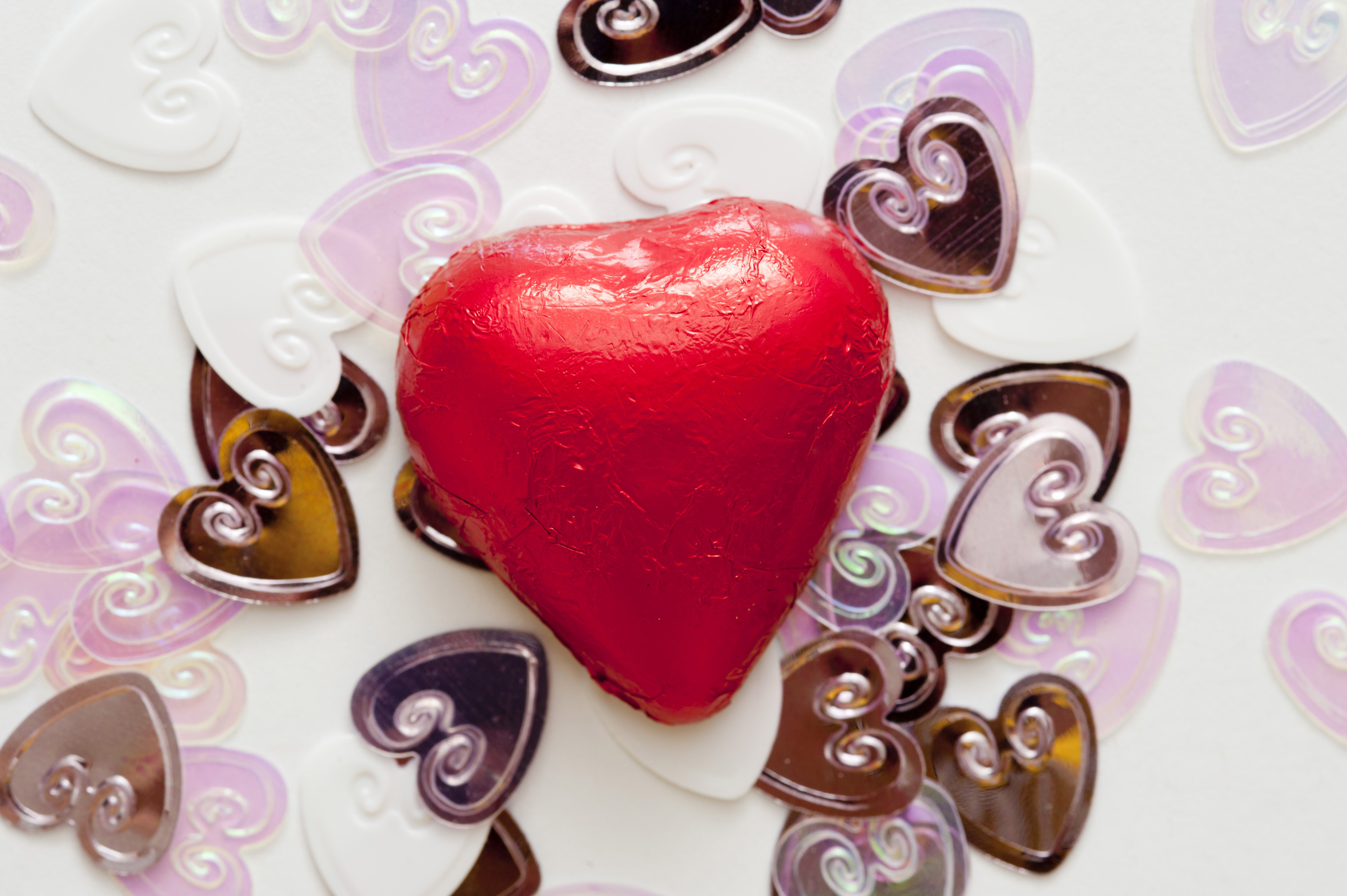 One red, chocolate valentine heart sits on top of a pile of smaller wedding heart decorations.