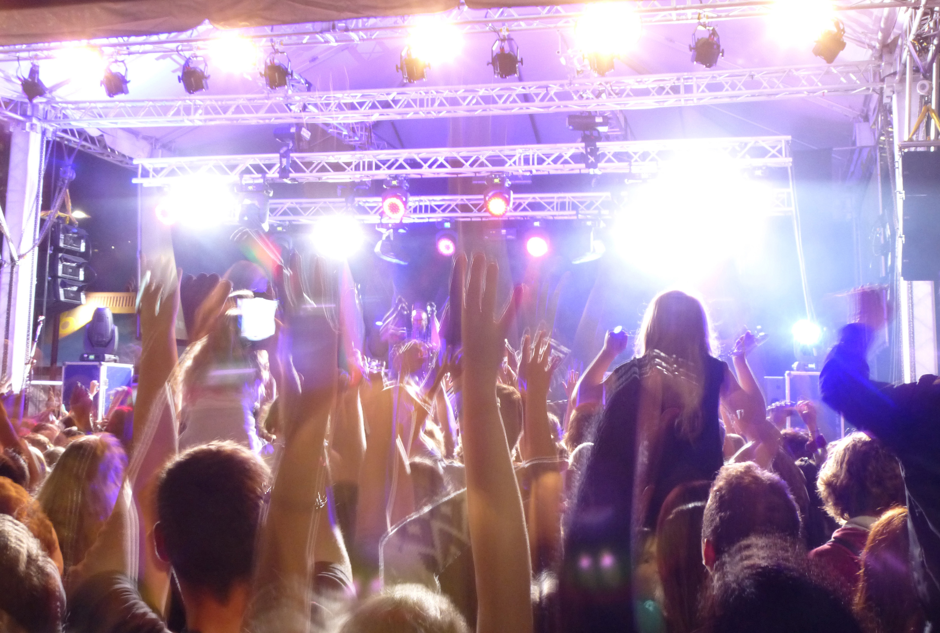People with raised hands attending a live performance on the stage during an entertaining concert, rear view