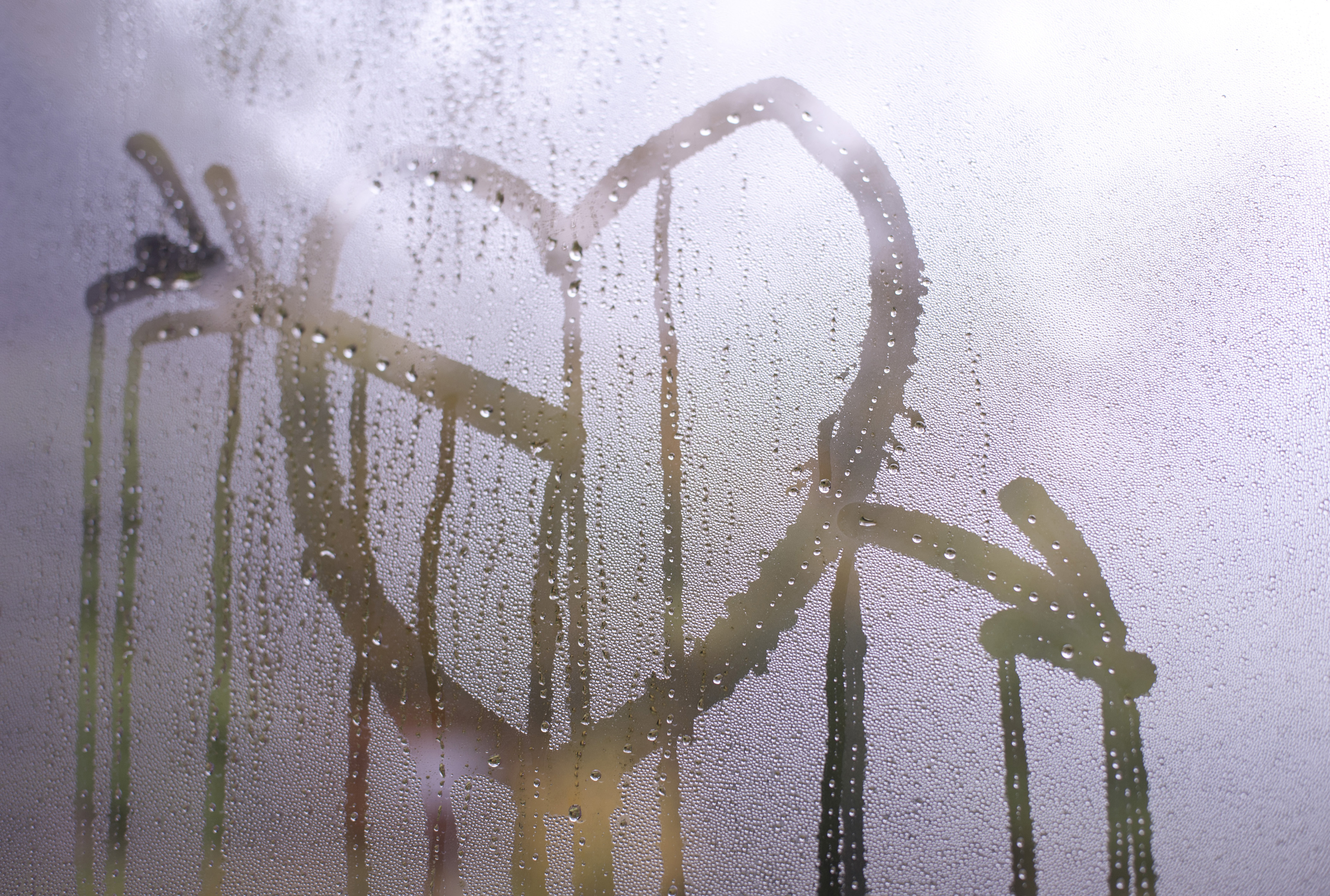 Romantic Valentines heart and Cupids arrow drawn in condensation on a glass windowpane with running rivulets of water for a sentimental message to a sweetheart