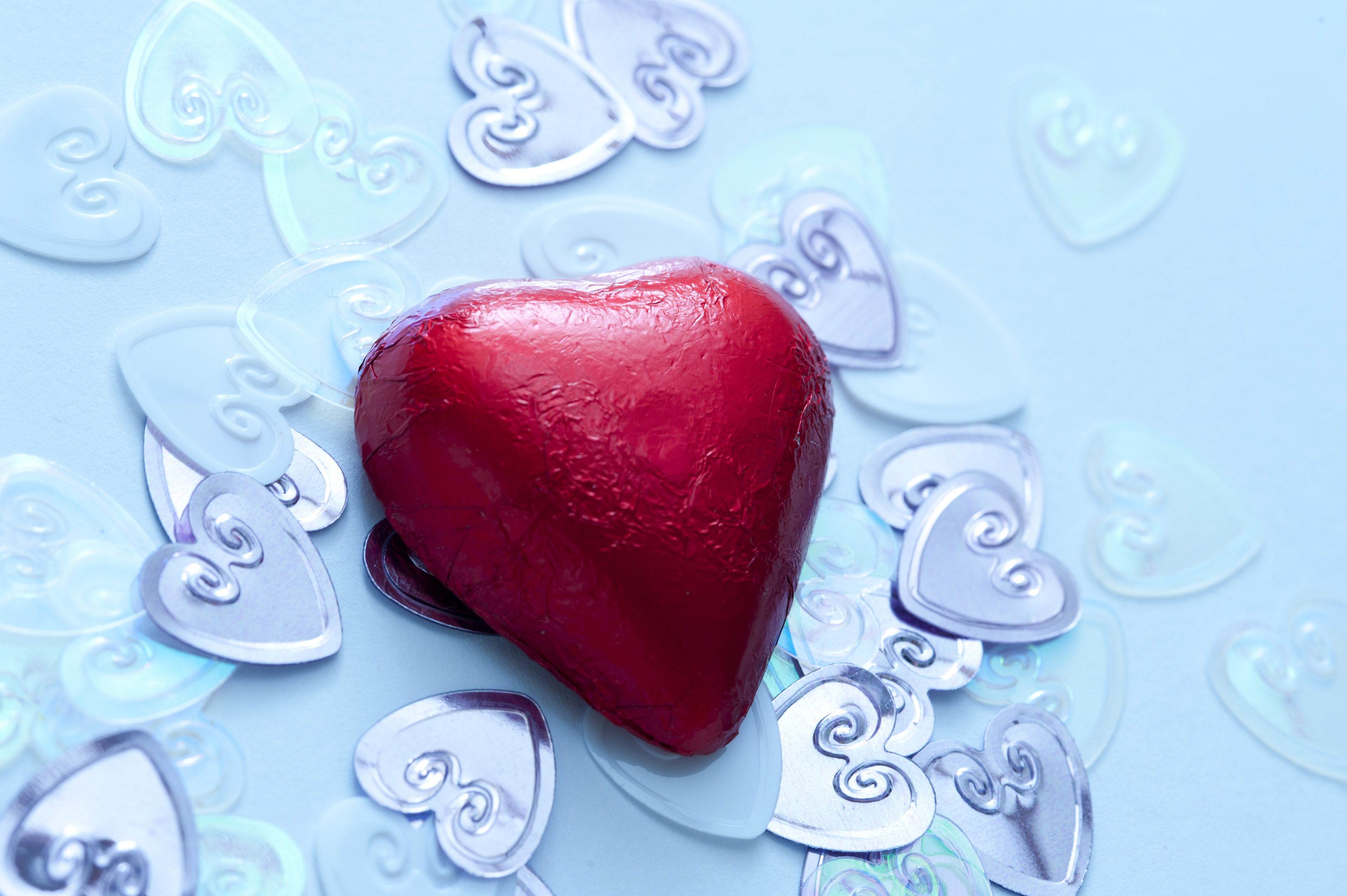 A single, red valentine chocolate on metallic wedding heart confetti decorations.