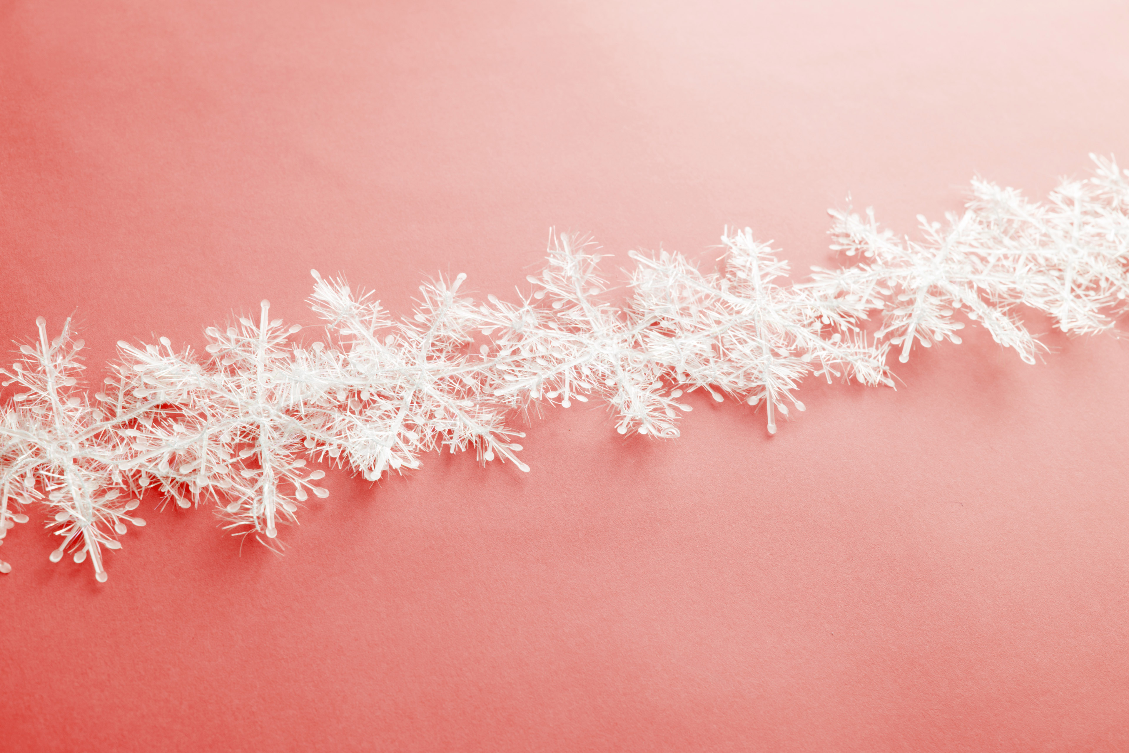 Decorative snowflake line lying against pink background