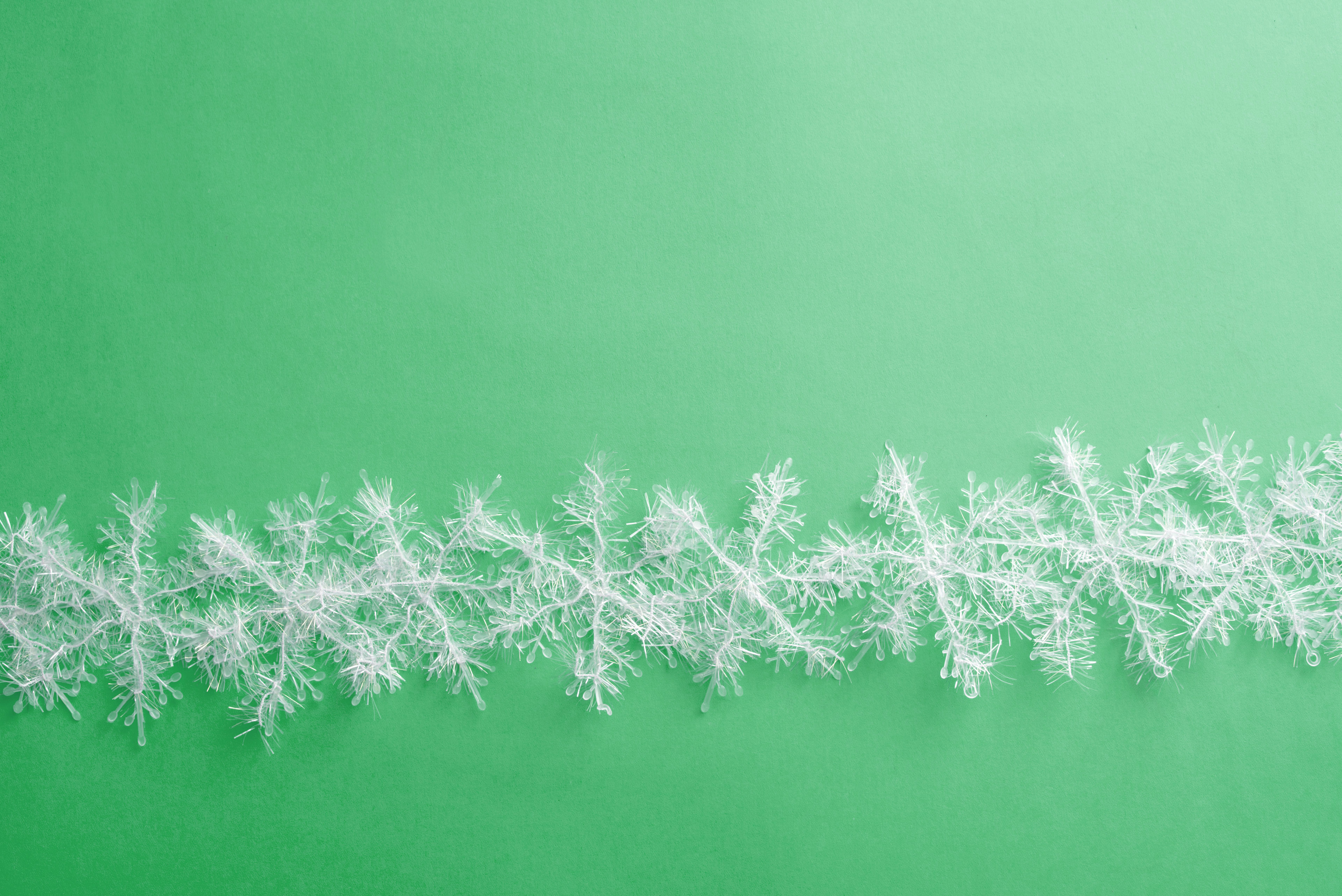 Decorative white Christmas snowflake wreath isolated on a plain green background.