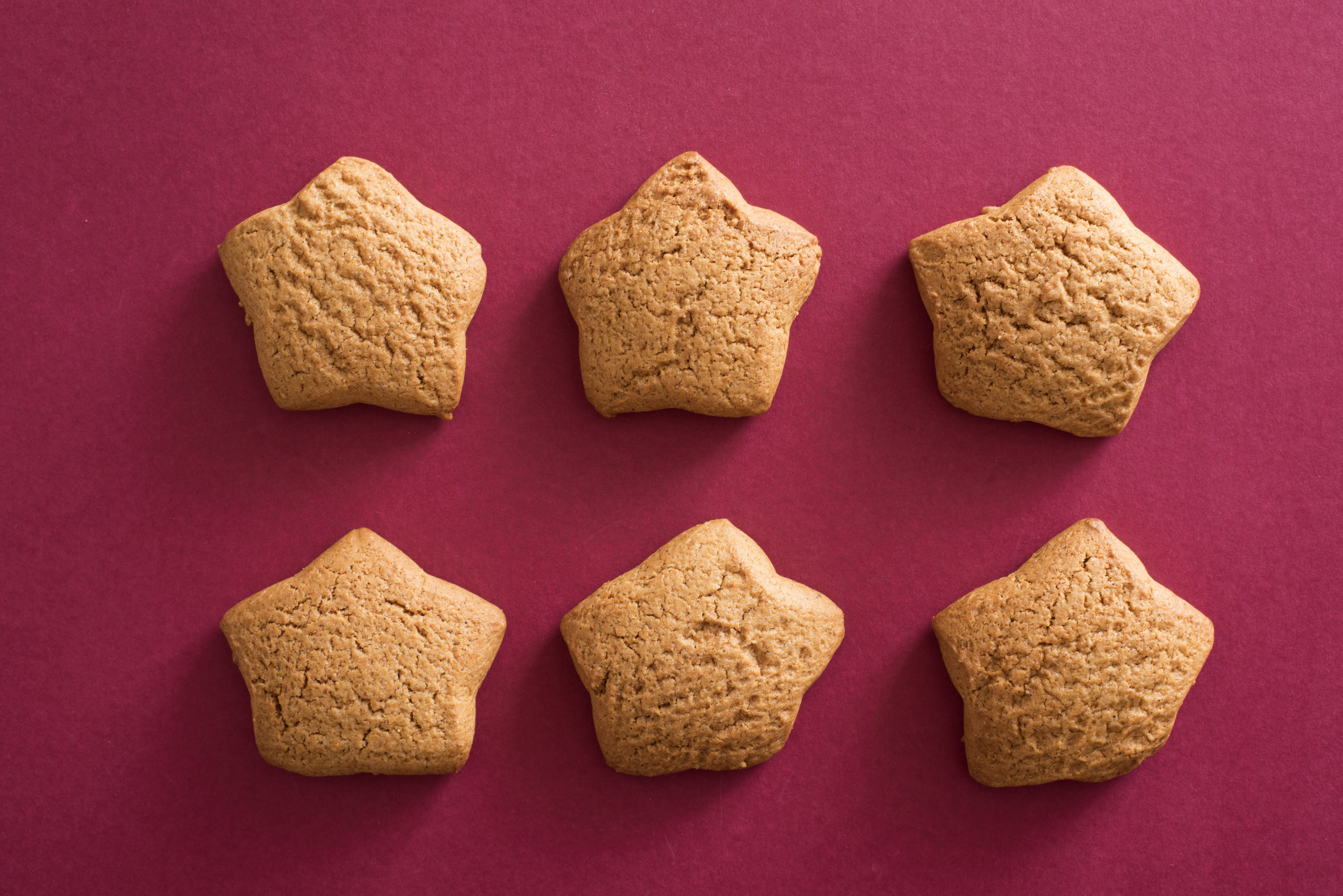 Six star shaped cookies in two rows on a festive red background for celebrating Christmas and New Year
